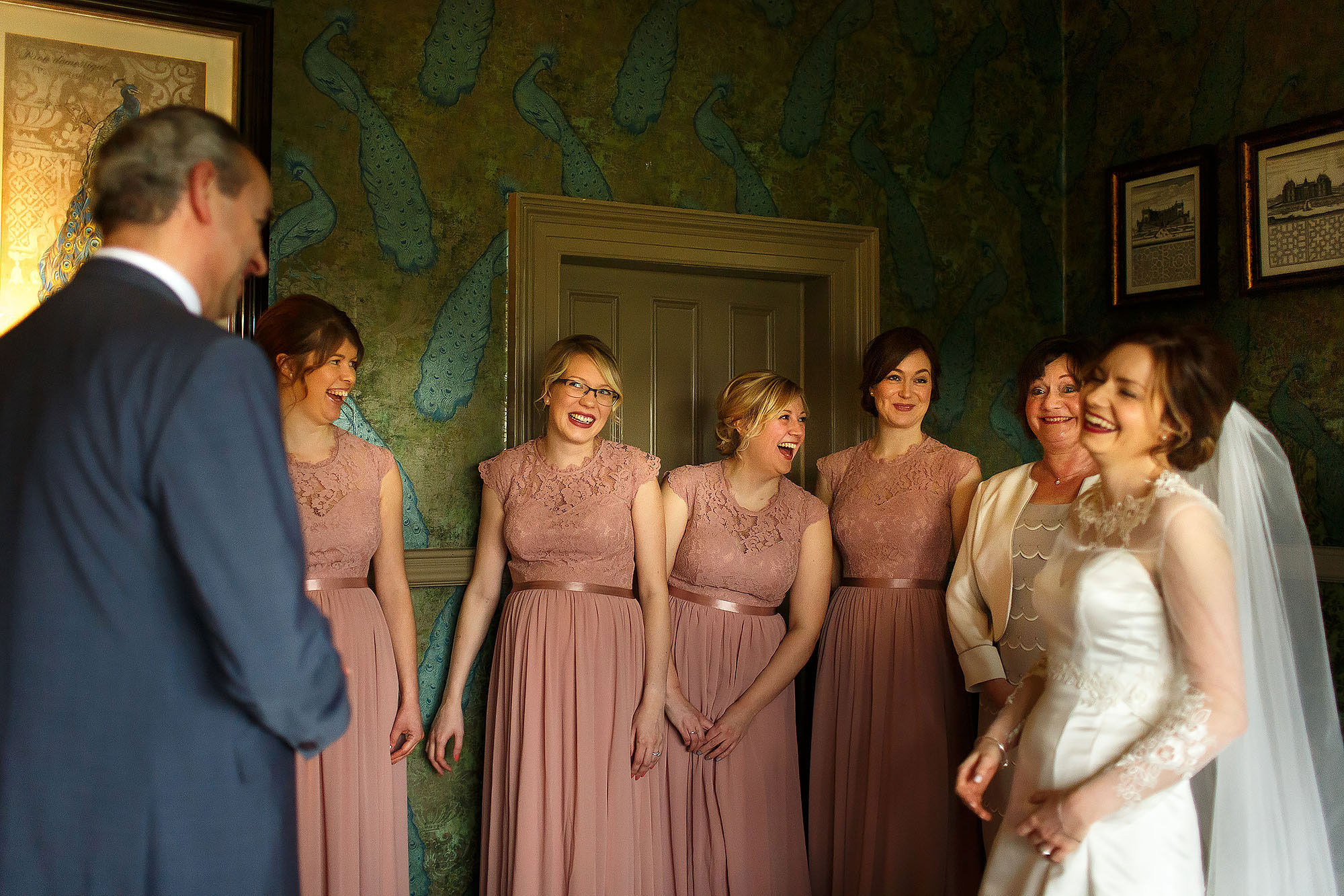 Bridesmaids all lined up wearing pink looking at the bride | Mitton Hall wedding photographs by Toni Darcy Photography