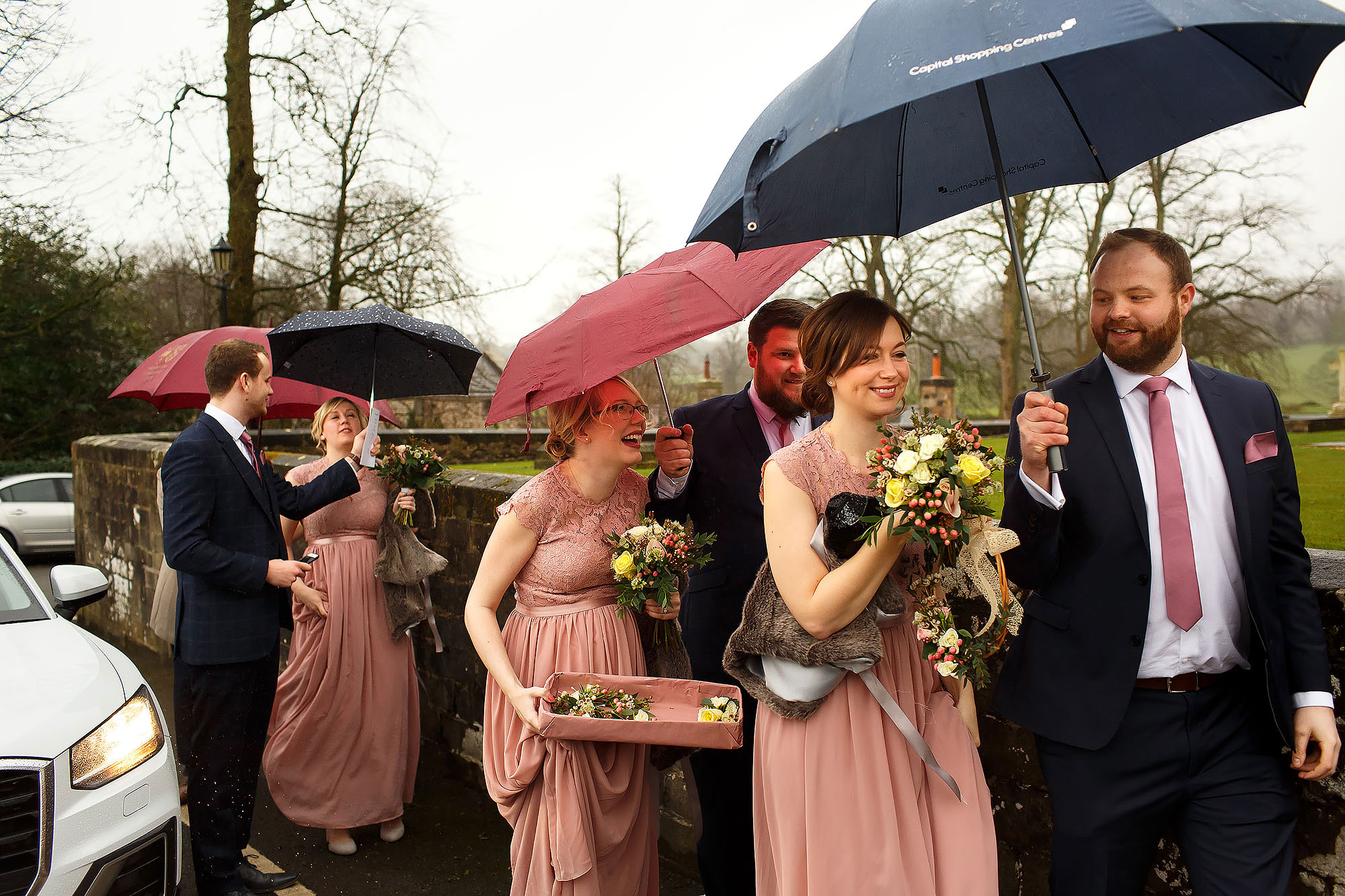 Bridesmaids arriving at Stonyhurst College holding umbrellas as they walk towards the church | Mitton Hall wedding photographs by Toni Darcy Photography