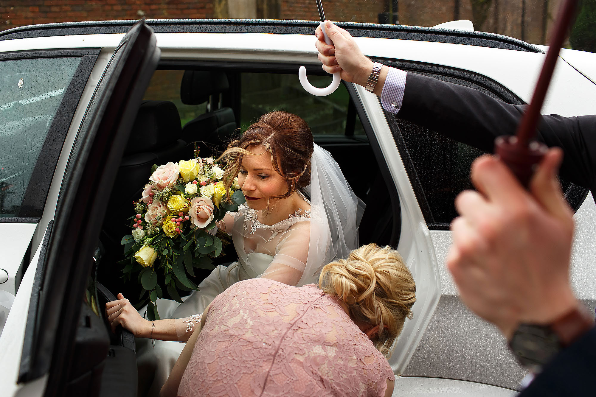 Bride stepping out of the wedding car at Stonyhurst as people hold umbrellas | Mitton Hall wedding photographs by Toni Darcy Photography