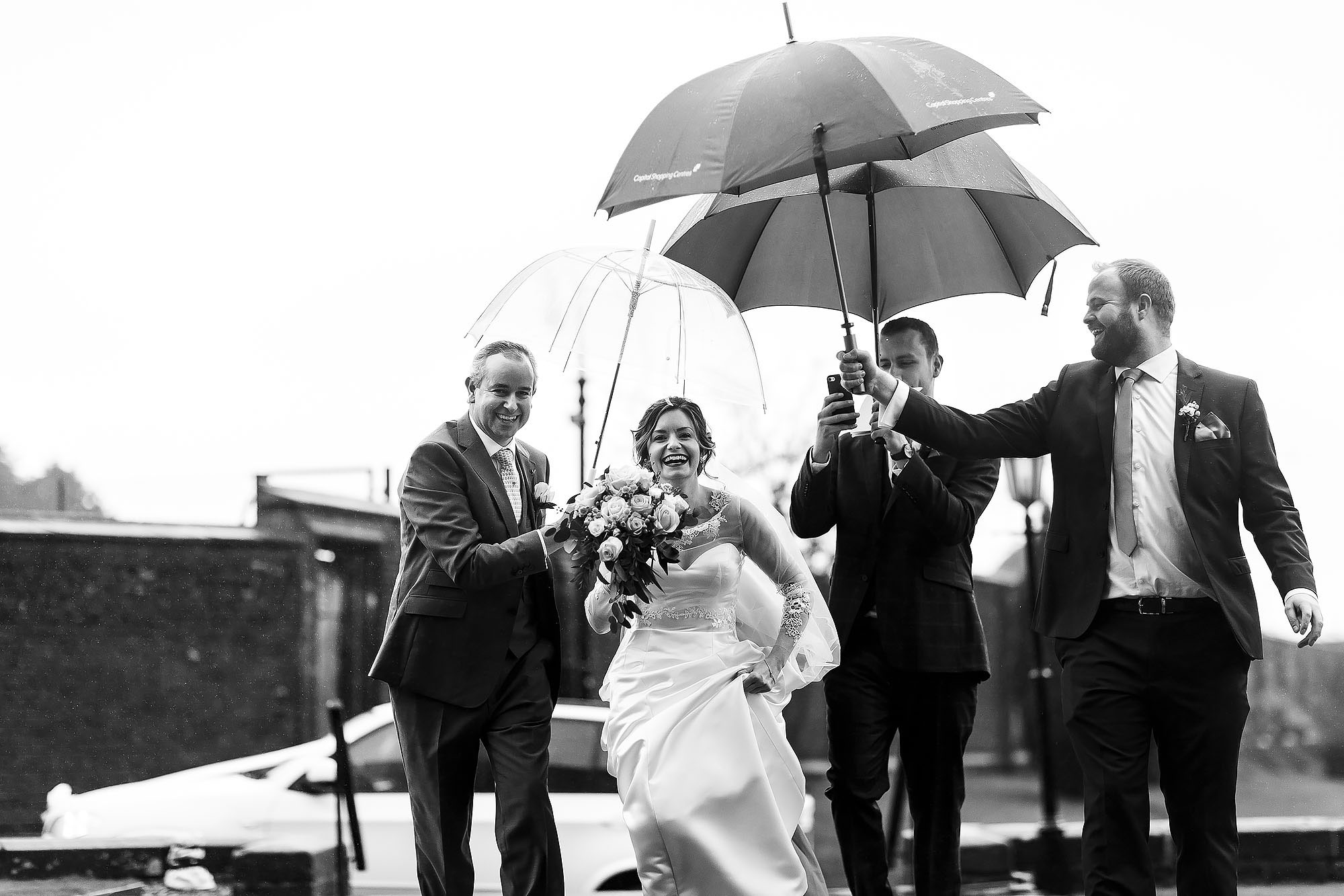 Bride walking into church at Stonyhurst college with numerous hands holding the dress and umbrellas | Mitton Hall wedding photographs by Toni Darcy Photography