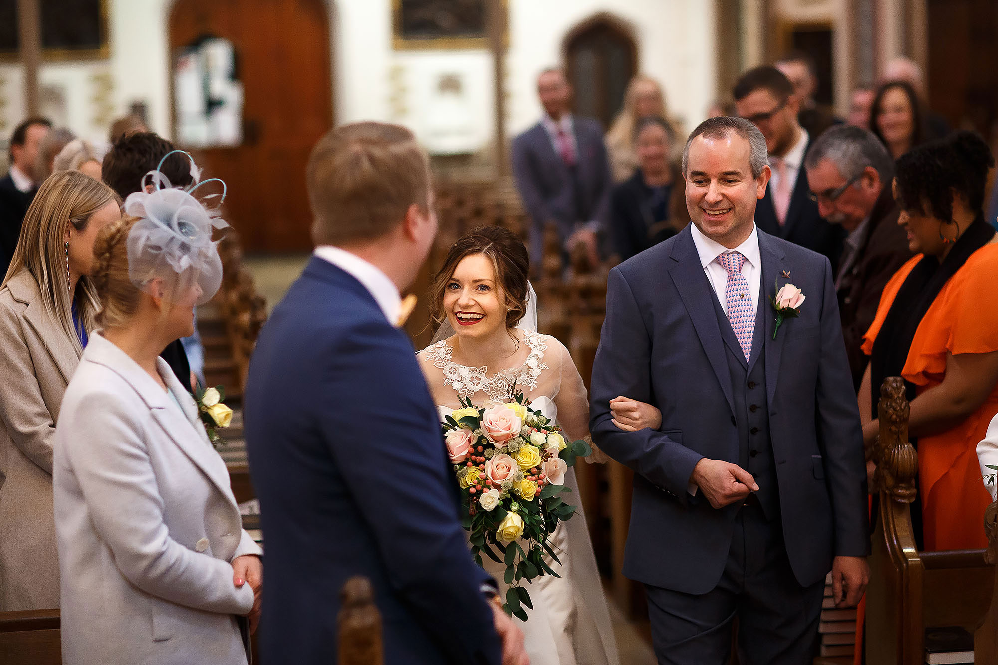 Bride looking excited as she locks eyes with the groom at the top of the wedding aisle | Mitton Hall wedding photographs by Toni Darcy Photography