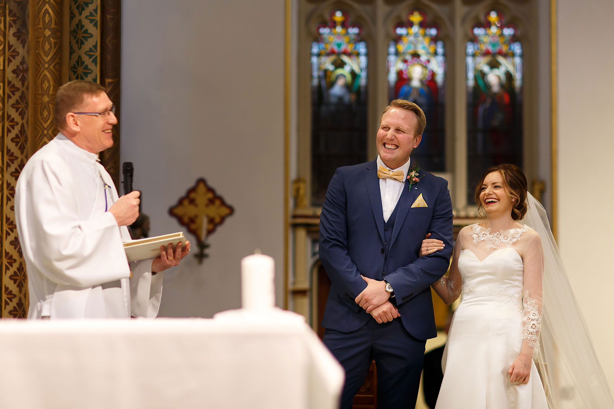 Bride and groom laughing at the altar inside Stonyhurst St Peters | Mitton Hall wedding photographs by Toni Darcy Photography