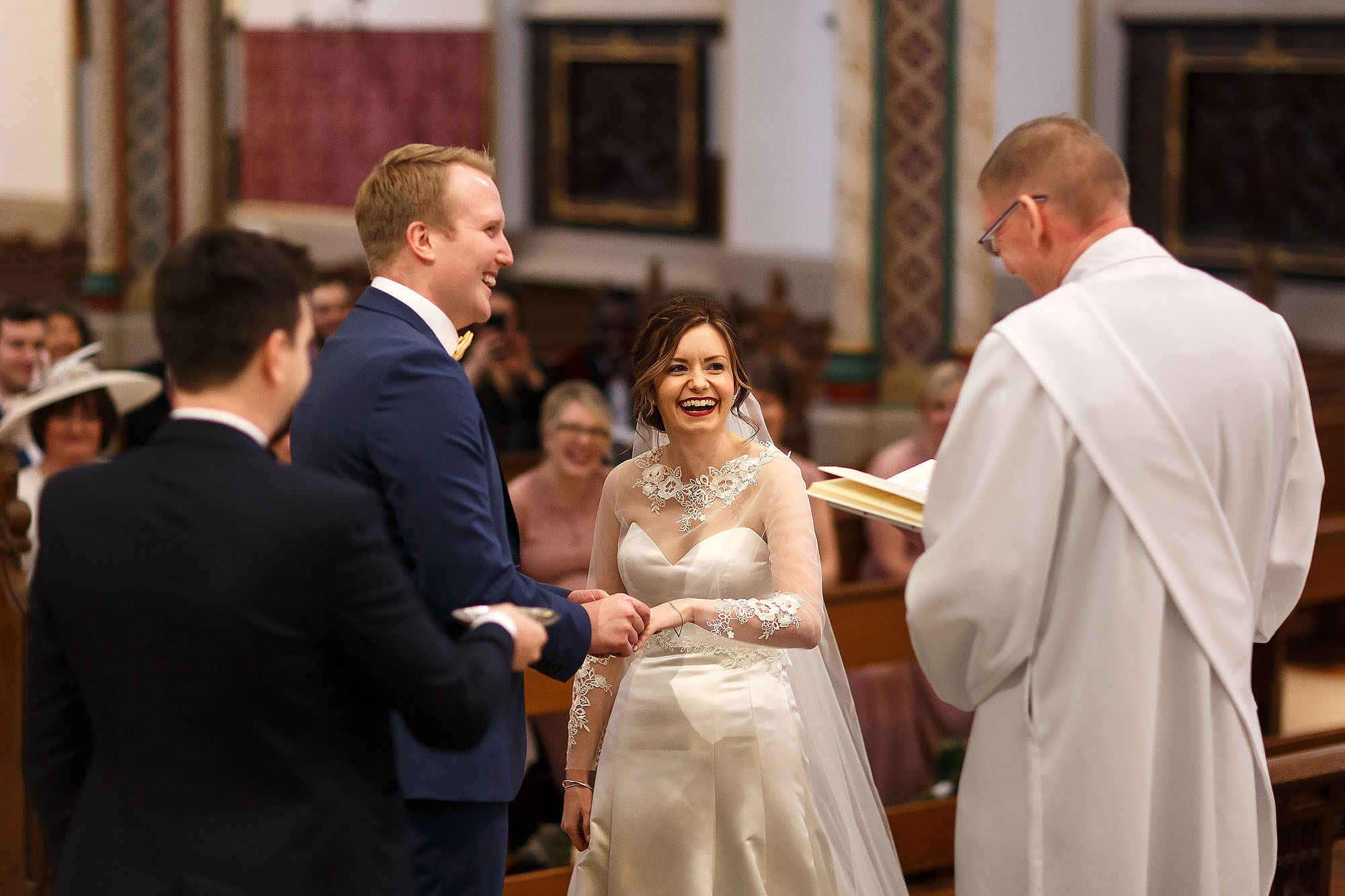 Bride and groom exchanging wedding rings during wedding ceremony at St Peters Stonyhurst | Mitton Hall wedding photographs by Toni Darcy Photography