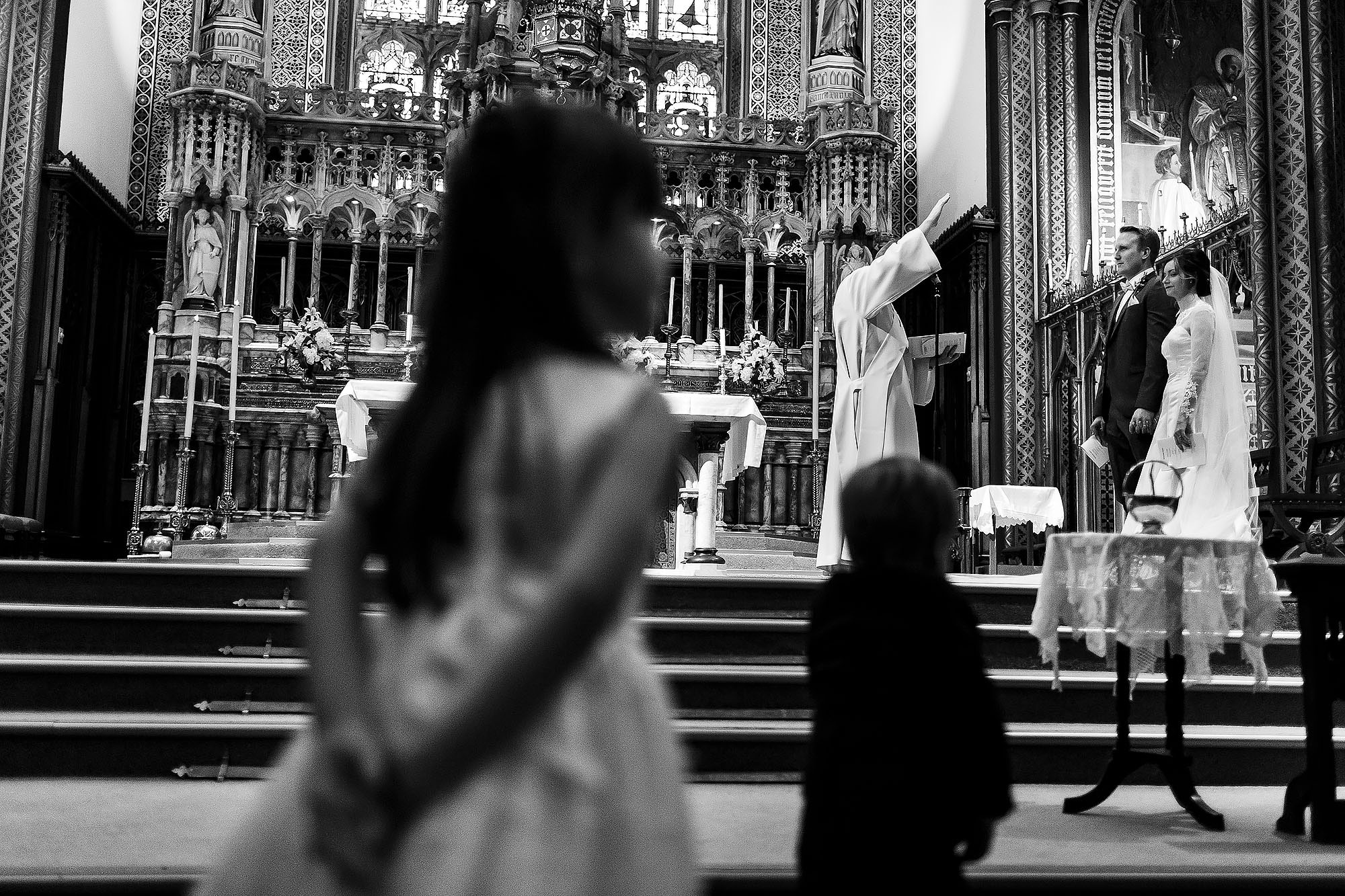 Bride and groom stood on the altar as page boy tries to join them at St Peters Stonyhurst | Mitton Hall wedding photographs by Toni Darcy Photography