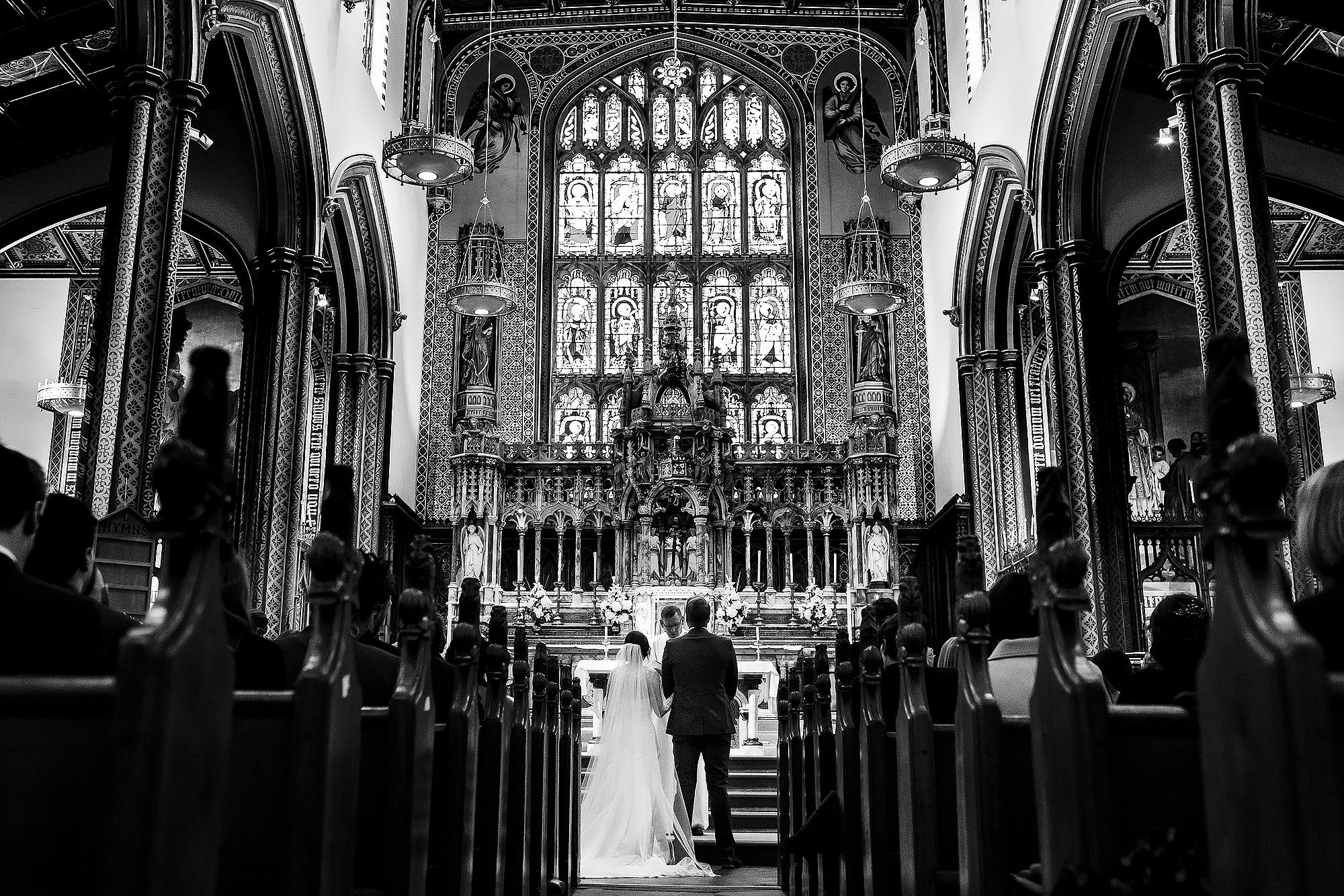 Wide view of bride and groom at the top of the aisle showing the full interior of St Peters Stonyhurst | Mitton Hall wedding photographs by Toni Darcy Photography