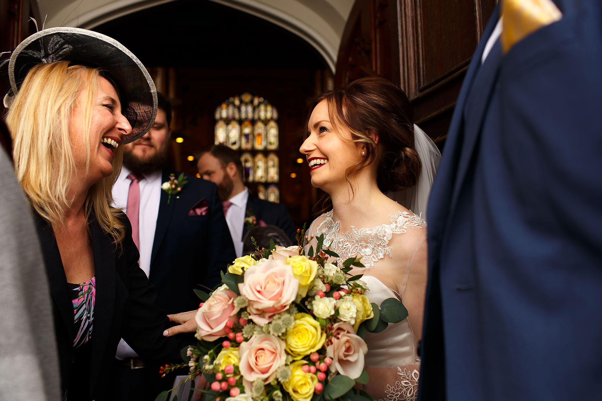 Bride and groom greeting wedding guests as they exit St Peters Stonyhurst after the wedding ceremony | Mitton Hall wedding photographs by Toni Darcy Photography