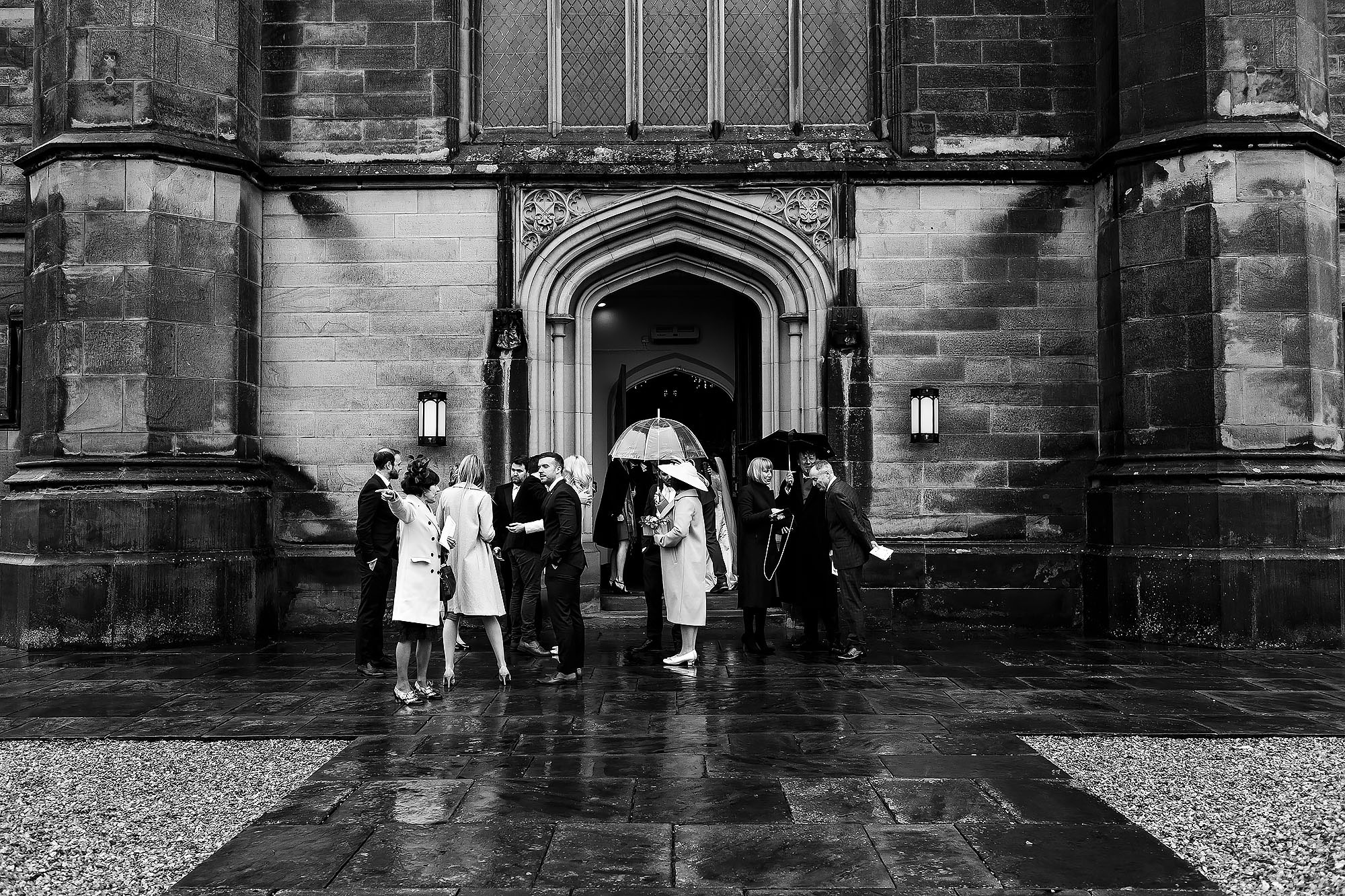 Wedding guests waiting outside St Peters Stonyhurst in the rain | Mitton Hall wedding photographs by Toni Darcy Photography