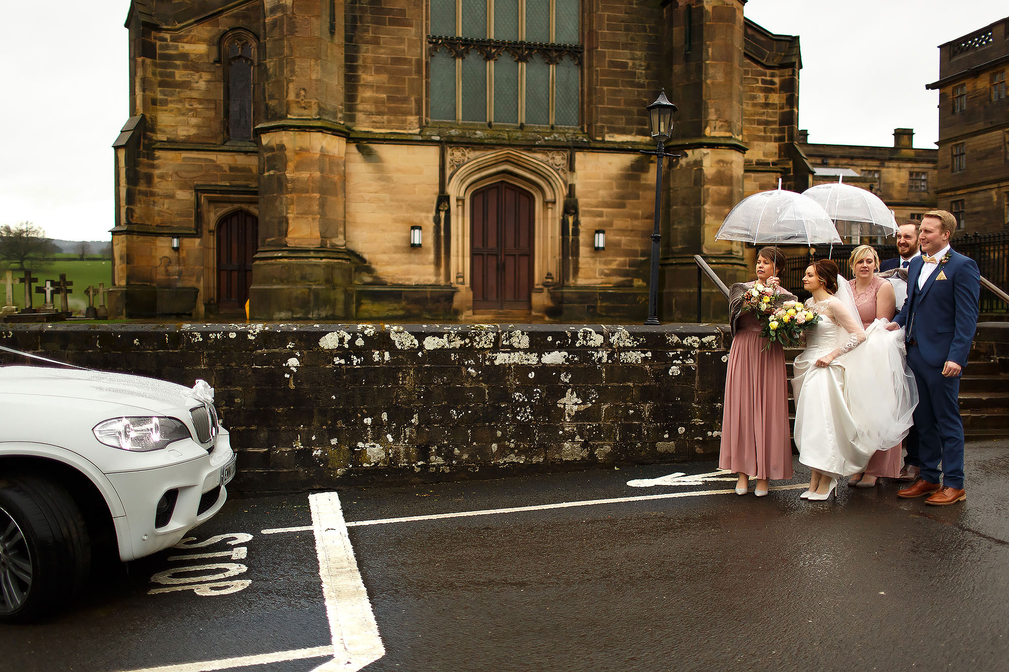 Bride and groom with bridesmaids waiting outside Stonyhurst St Peters for the wedding car | Mitton Hall wedding photographs by Toni Darcy Photography