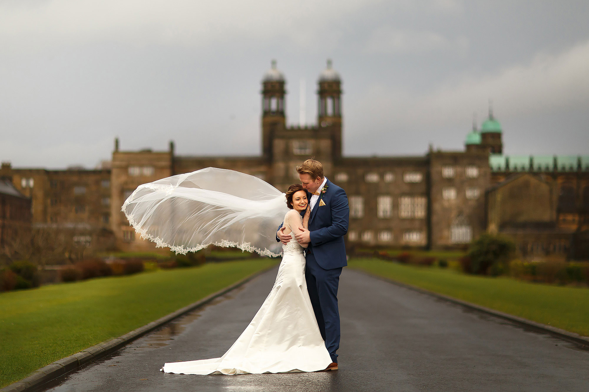 Bride wearing long sleeved wedding dress and long wedding veil holding tight onto her groom wearing royal blue suit with mustard pocket square and bow tie stood on the long driveway leading to Stonyhurst College | Mitton Hall wedding photographs by Toni Darcy Photography