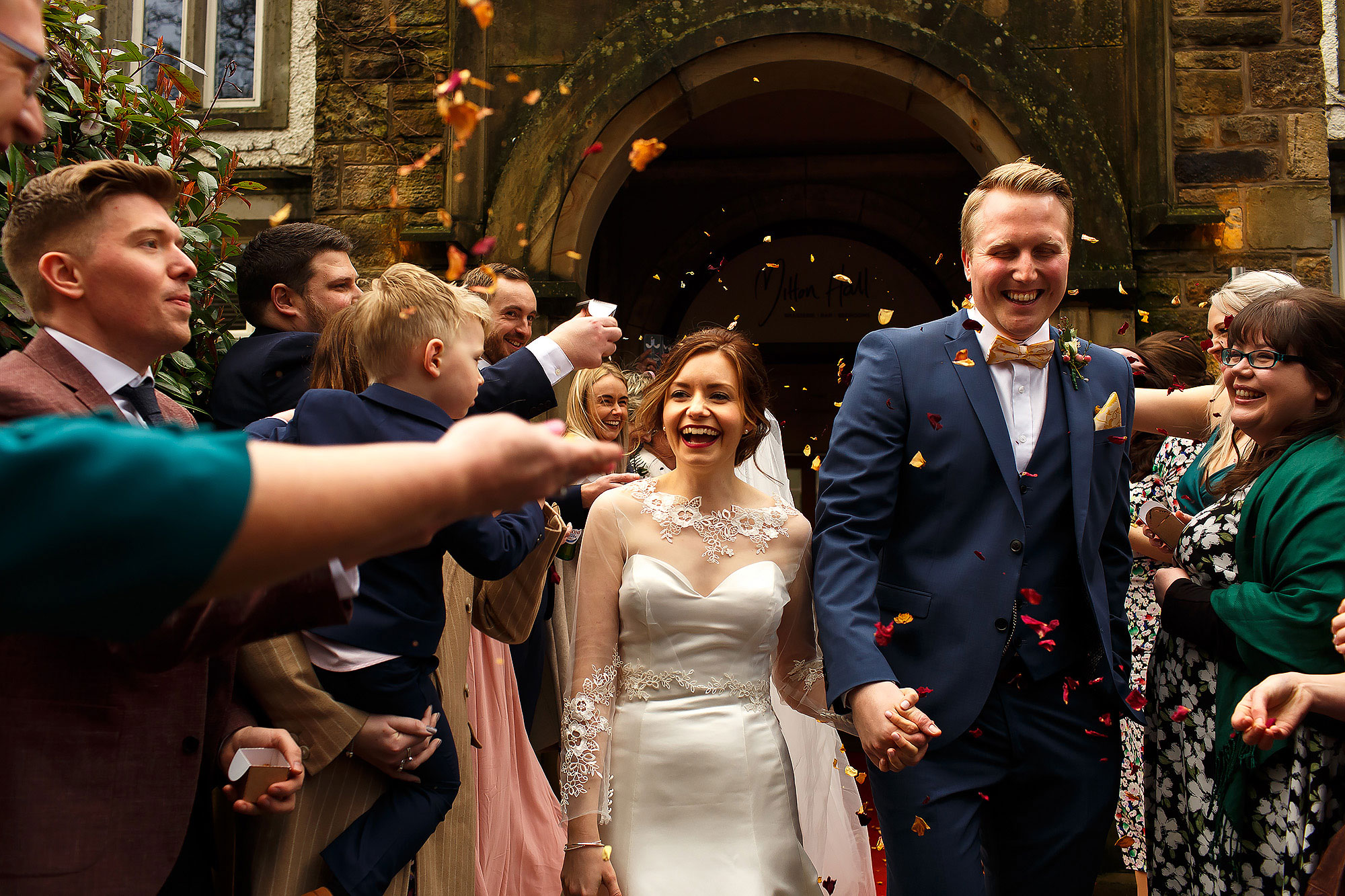 Bride and groom walking outside the wedding reception of Mitton Hall as the wedding guests throw confetti | Mitton Hall wedding photographs by Toni Darcy Photography