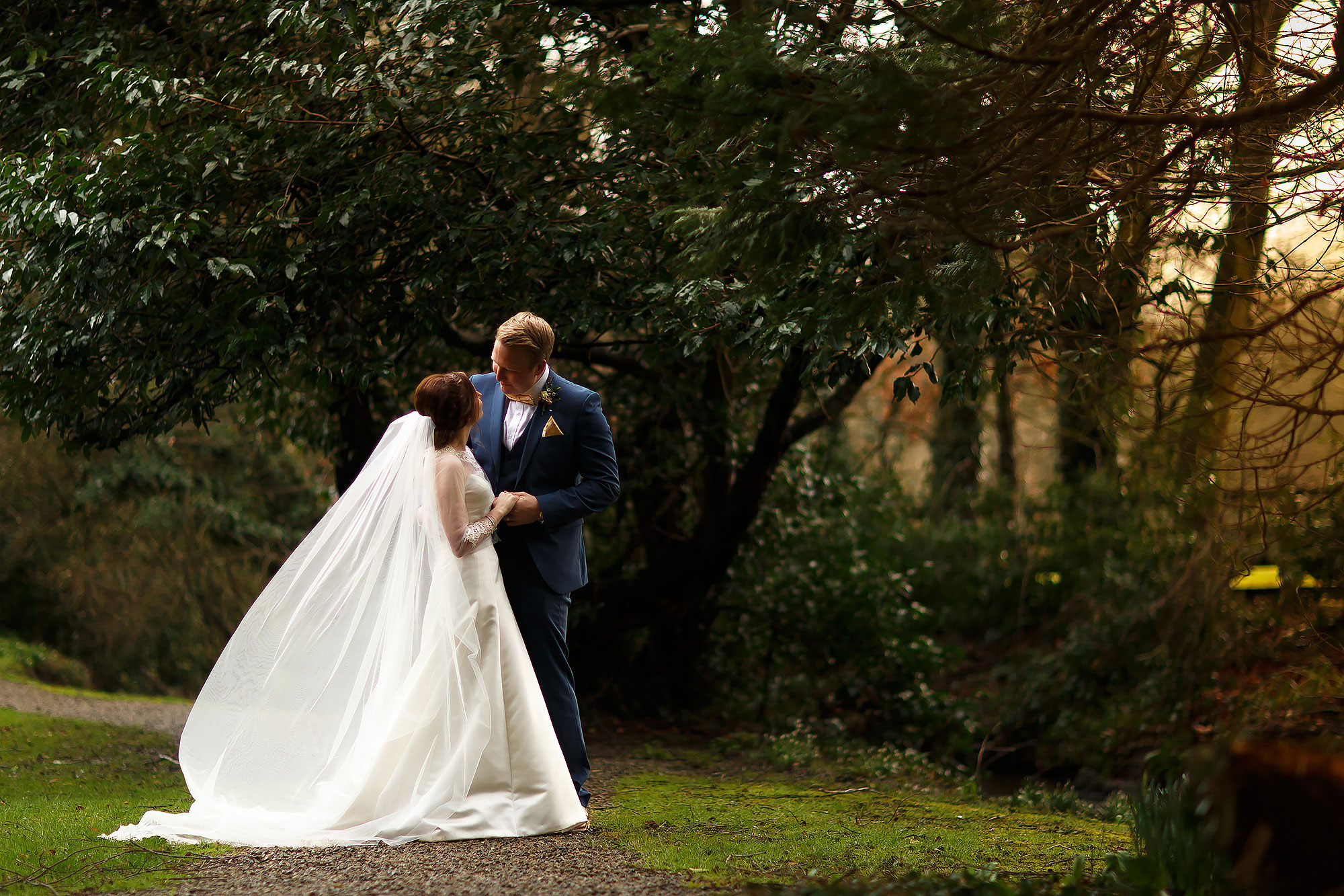 Bride and groom looking towards one another as the long wedding veil flows in the wind in the gardens of Mitton Hall | Mitton Hall wedding photographs by Toni Darcy Photography