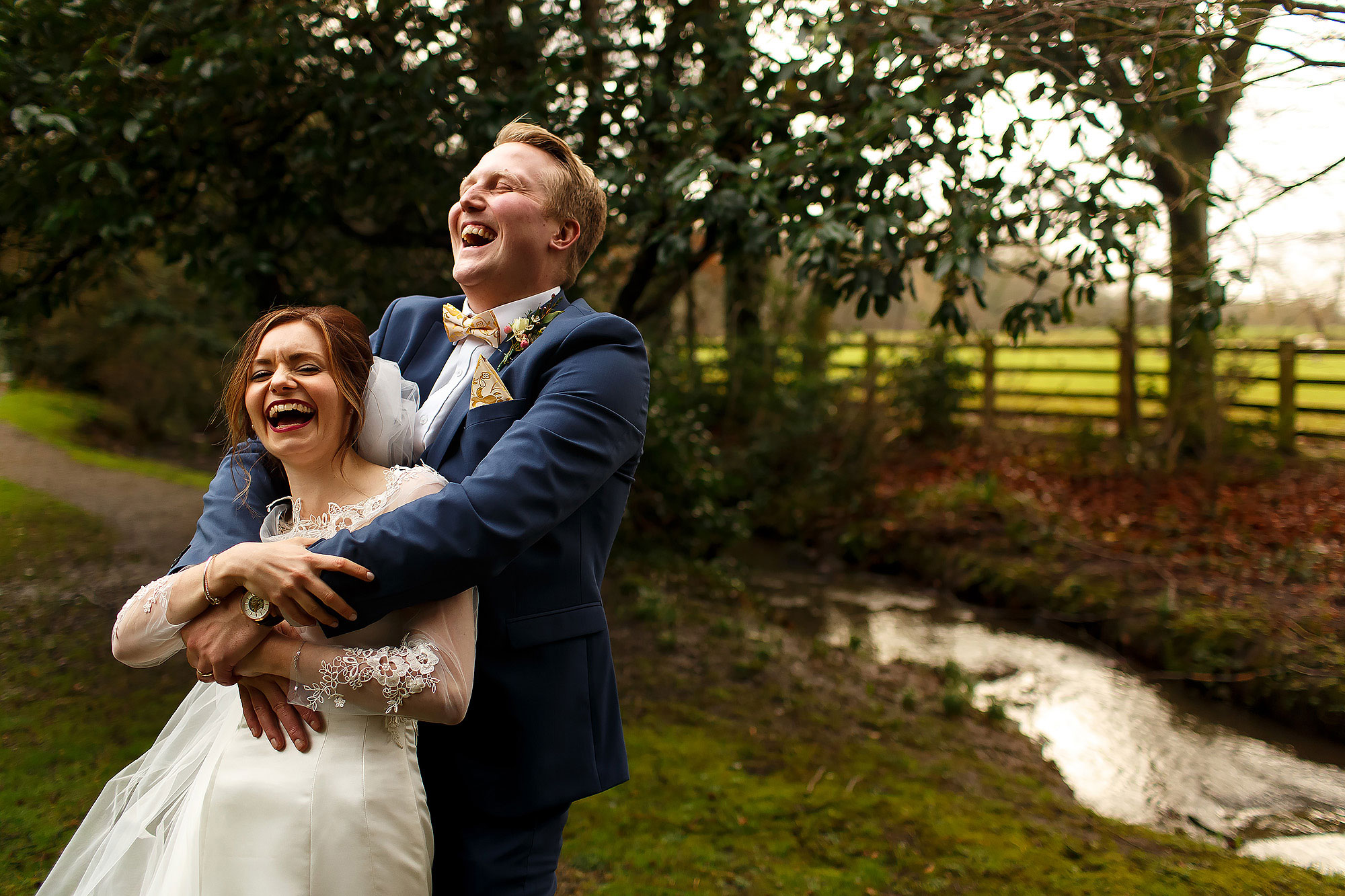 Bride with dark lipstick and long veil laughing in the arms of her groom wearing blue suit and yellow bow tie belly laughing in the gardens of Mitton Hall | Mitton Hall wedding photographs by Toni Darcy Photography
