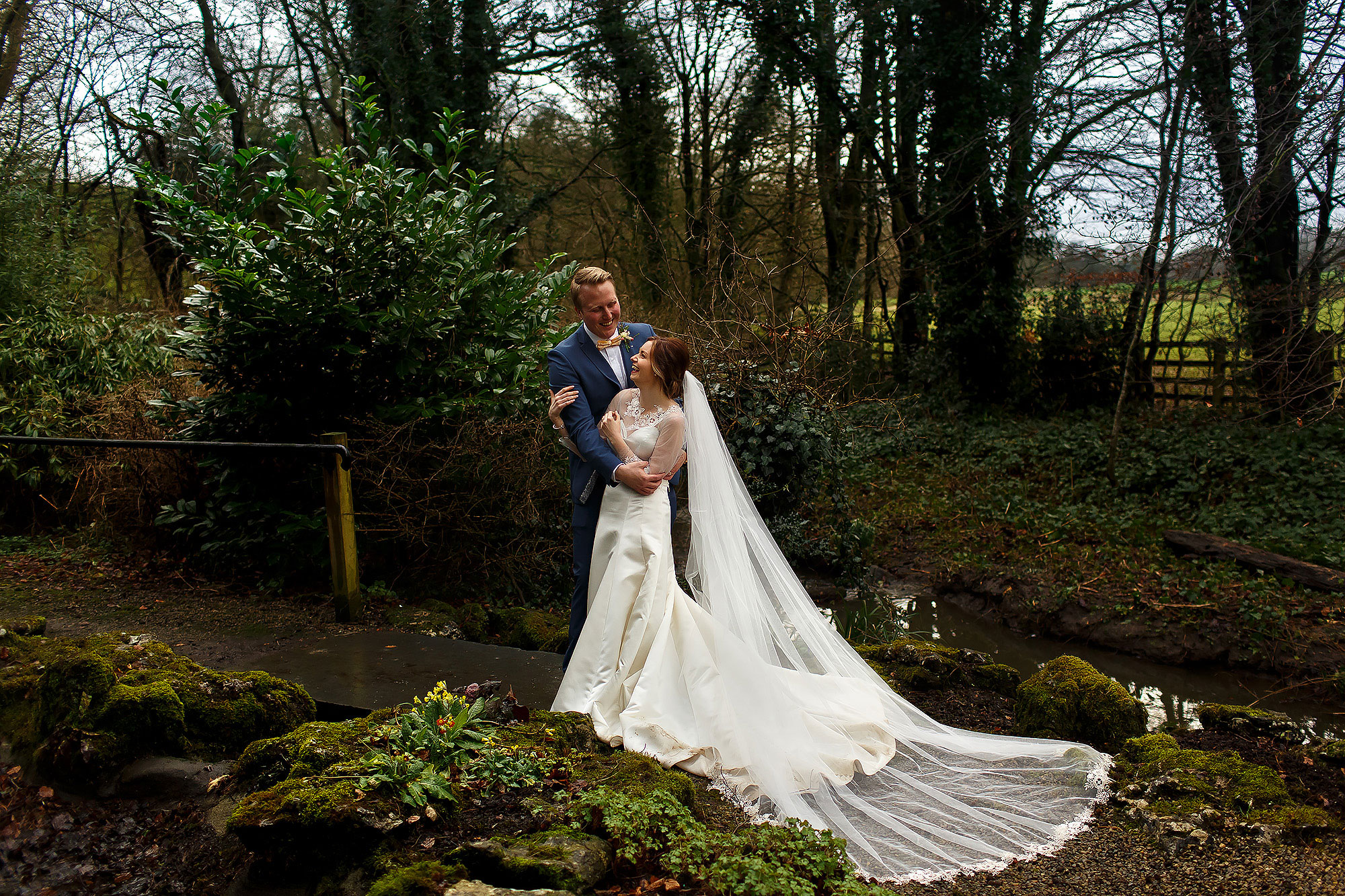 Bride and groom in the woodland gardens of Mitton Hall with long train of wedding dress flowing and long cathedral veil laid our perfectly | Mitton Hall wedding photographs by Toni Darcy Photography