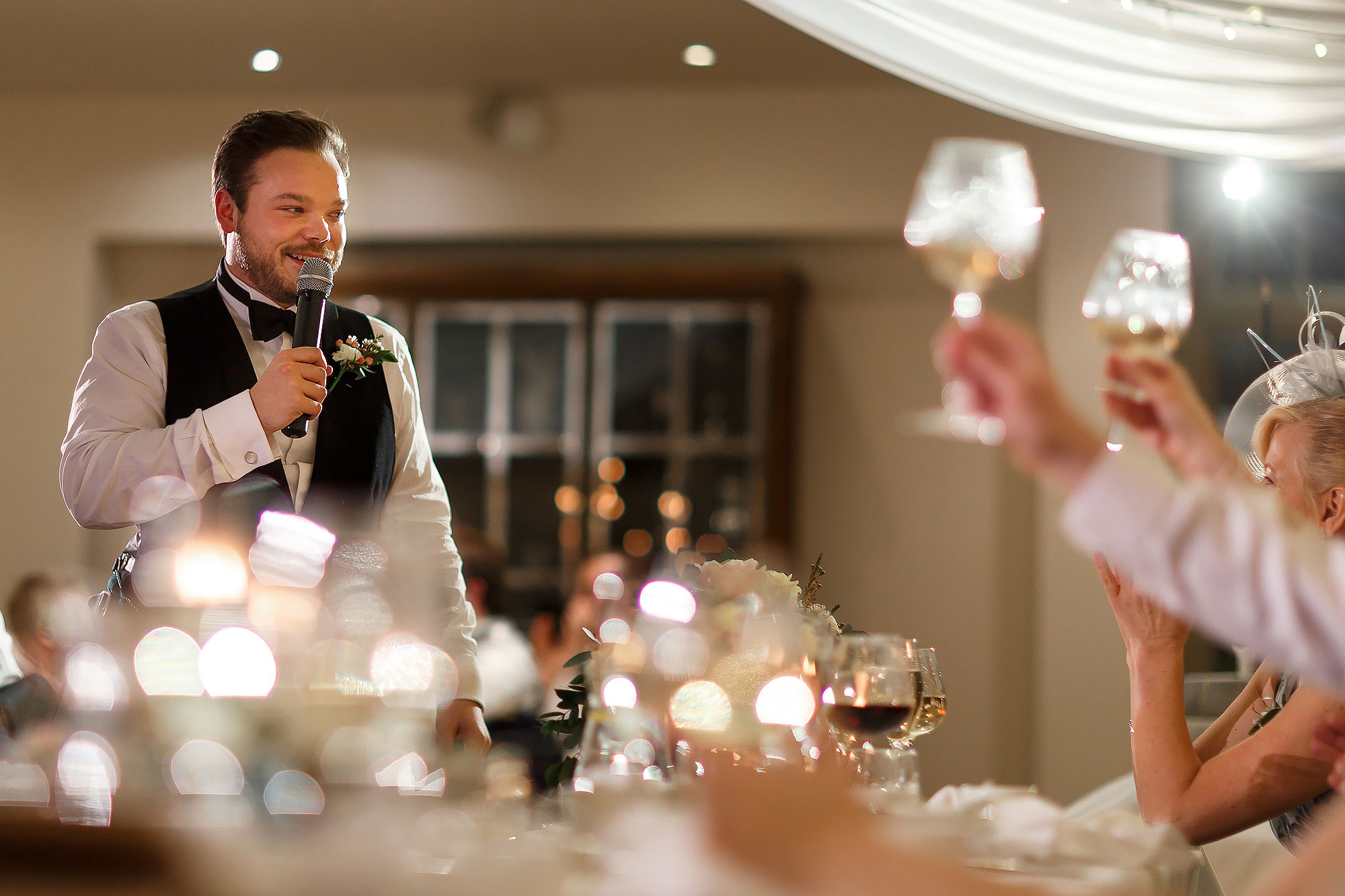 Best man toasting the bride and groom as guests wave their glasses | Mitton Hall wedding photographs by Toni Darcy Photography