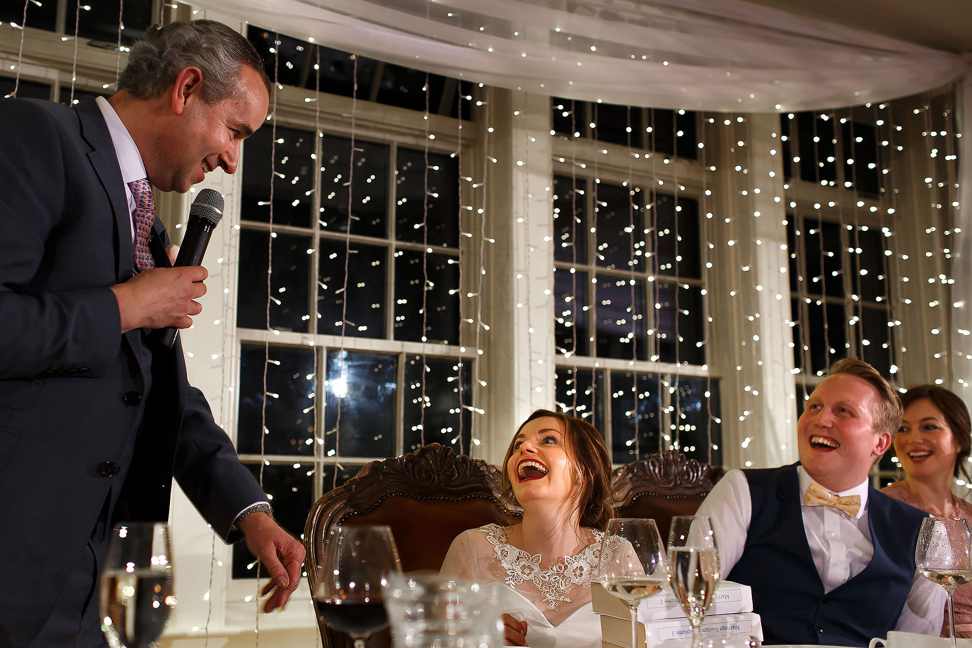 Bride and groom laughing with mouths wide open during the wedding speeches | Mitton Hall wedding photographs by Toni Darcy Photography