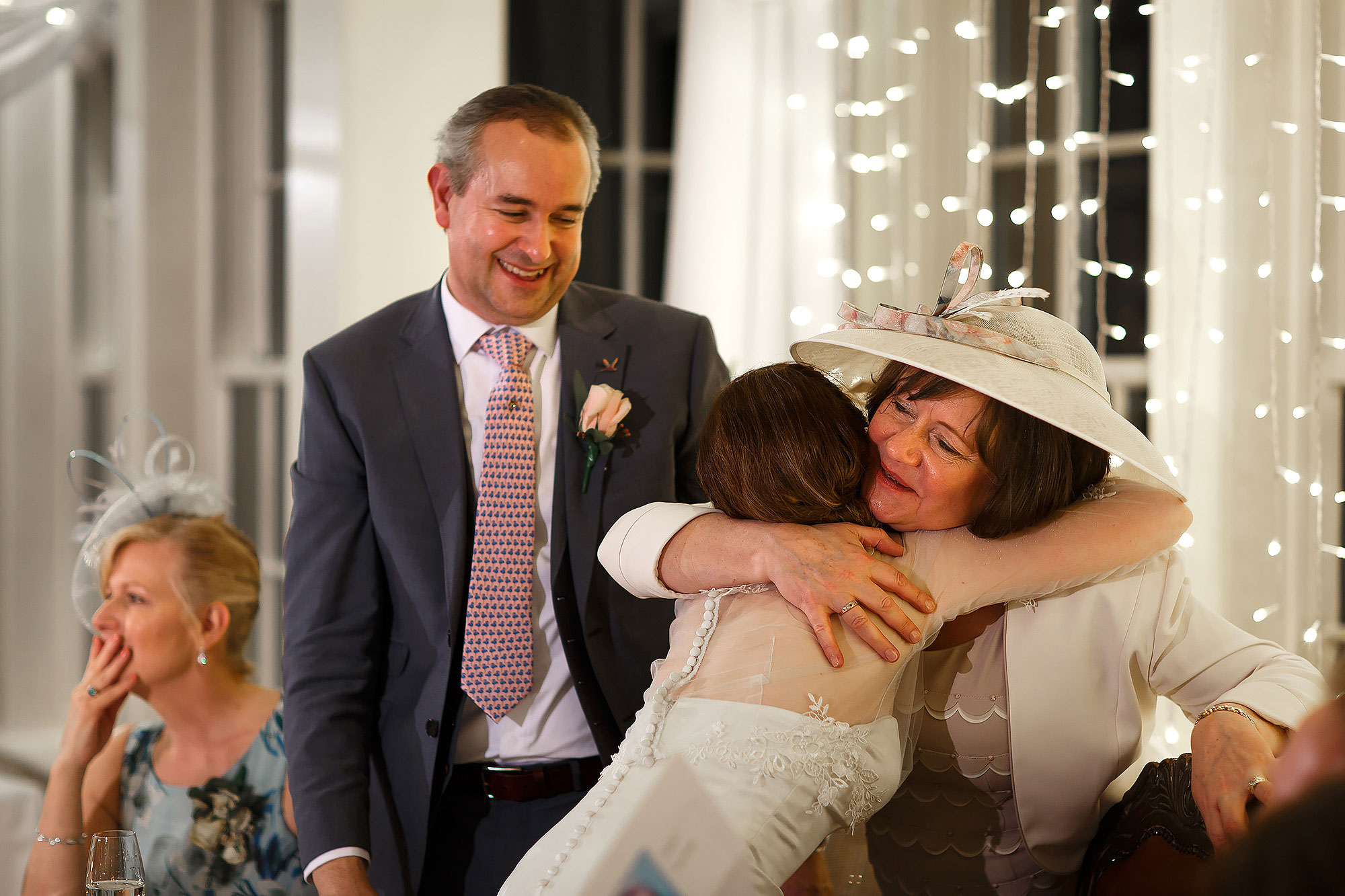 Bride and groom hugging the wedding guests on the top table | Mitton Hall wedding photographs by Toni Darcy Photography