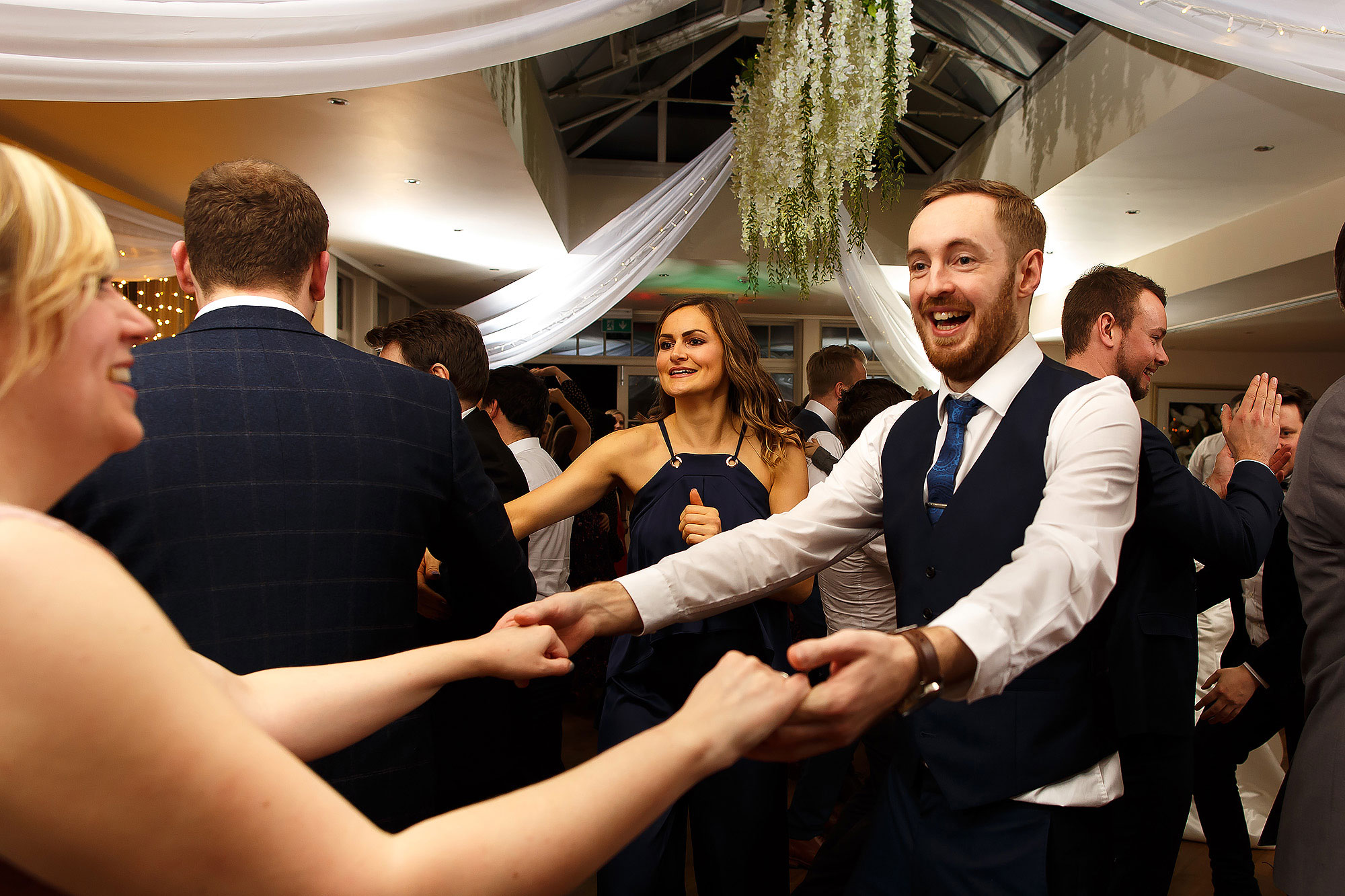 Wedding guests enjoying the ceilidh dancing | Mitton Hall wedding photographs by Toni Darcy Photography