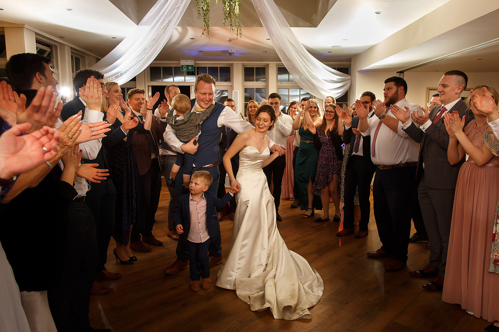 Bride and groom in the middle of the dance floor as the wedding guests surround them cheering | Mitton Hall wedding photographs by Toni Darcy Photography