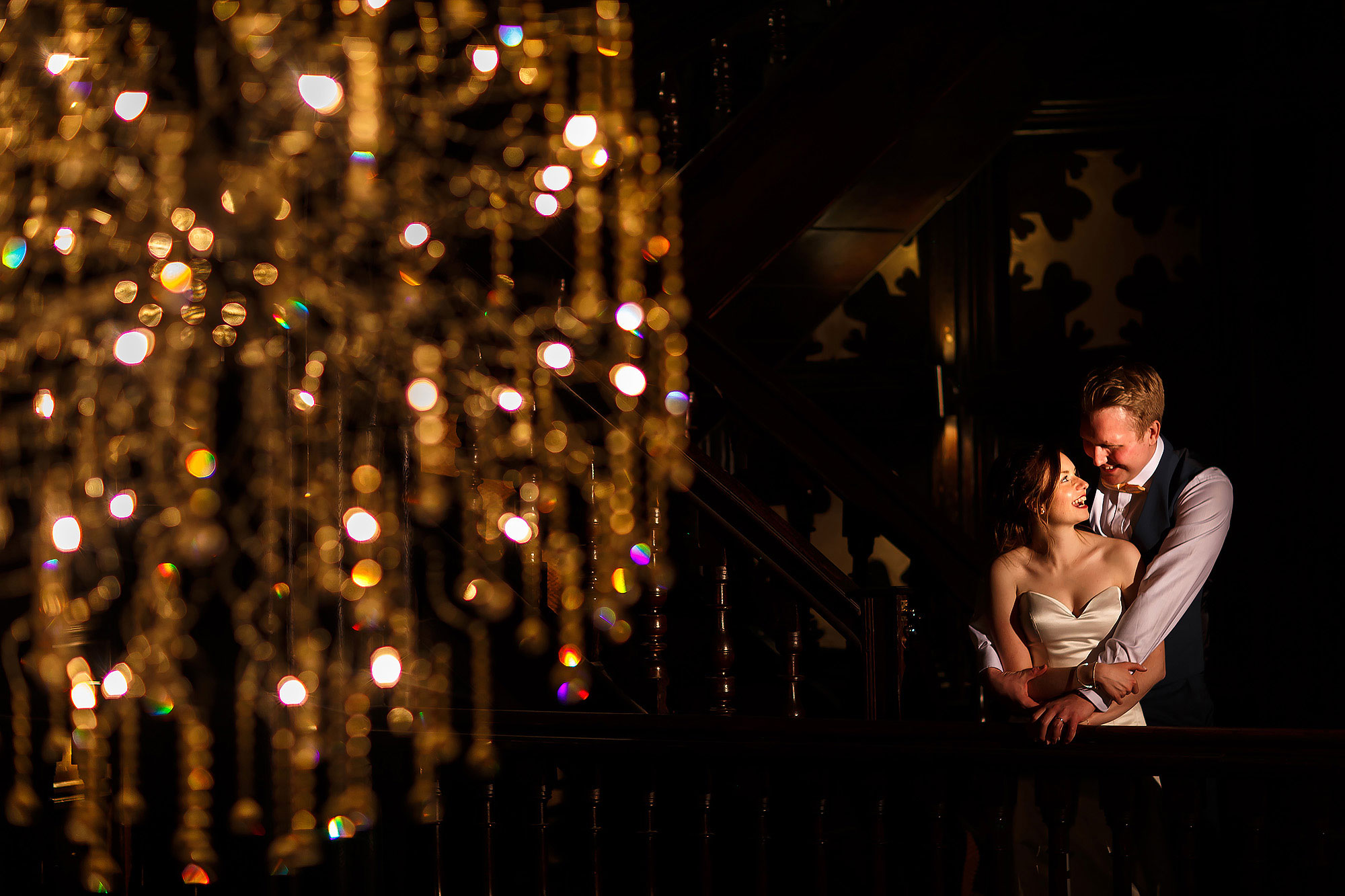 Bride and groom stood on the balcony inside Mitton Hall with large chandelier lighting them | Mitton Hall wedding photographs by Toni Darcy Photography