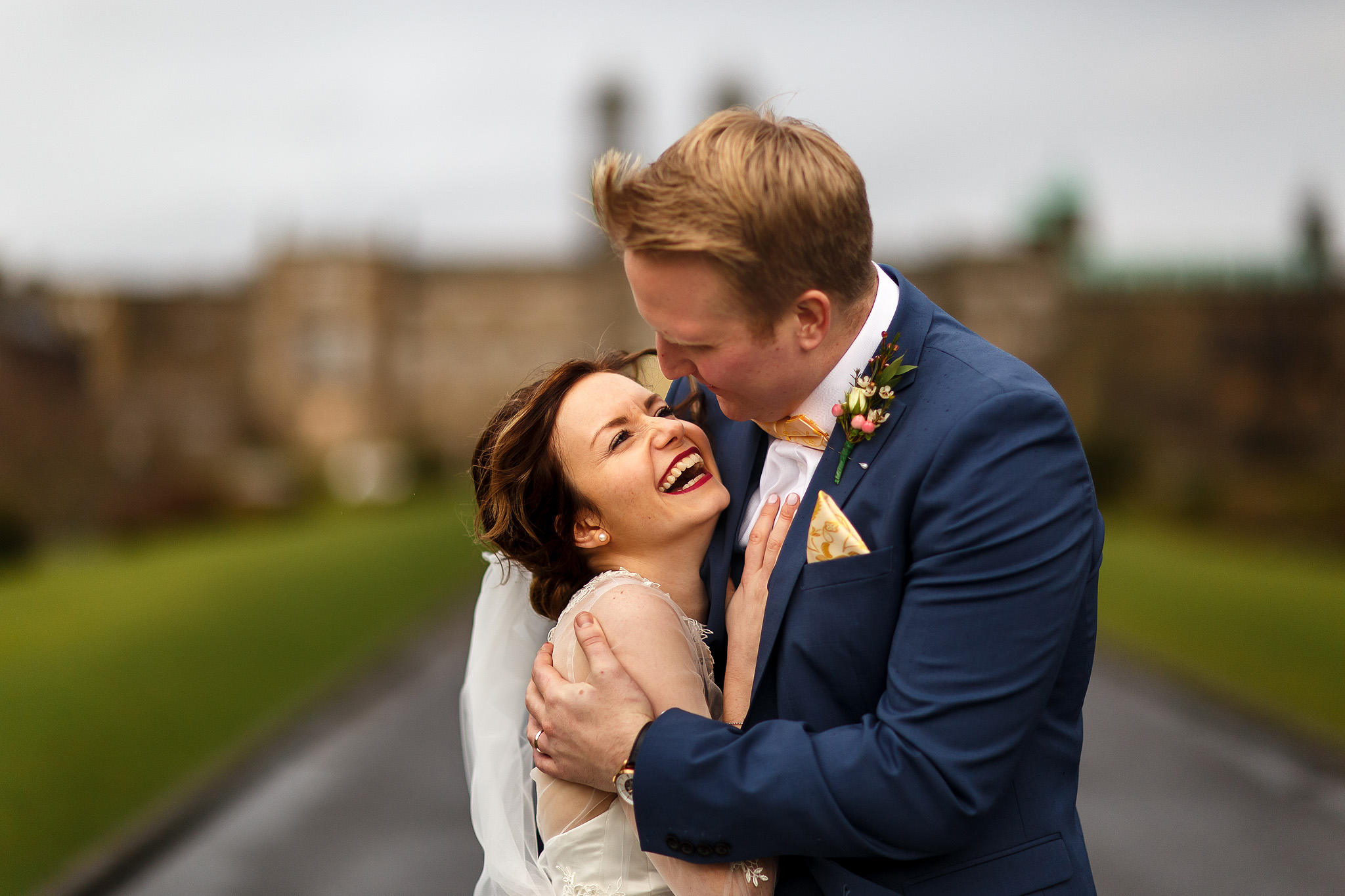 Bride with brunette hair and dark lipstick laughing in her grooms arms outside Stonyhurst College.