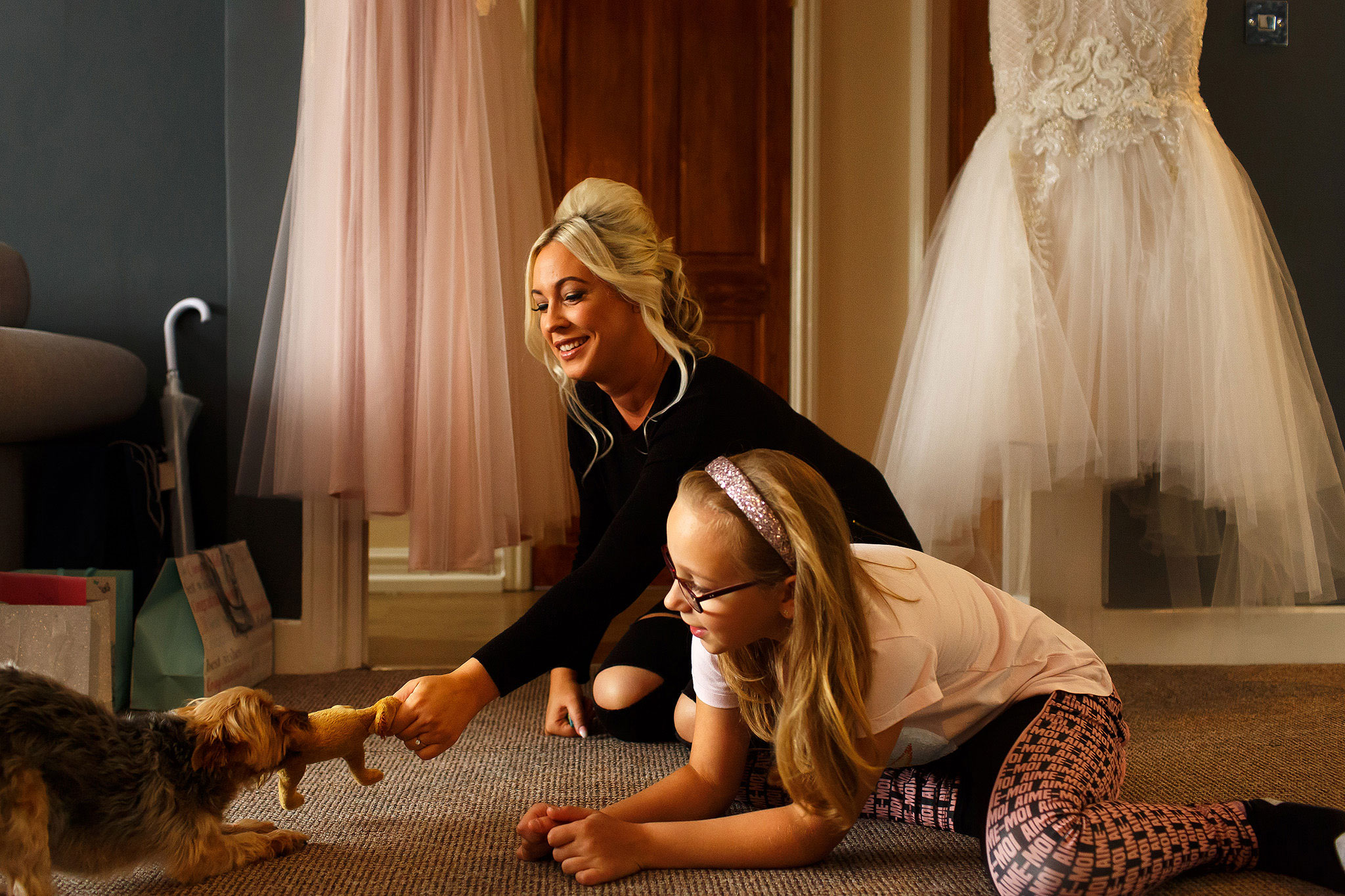 Bride playing with small brown dog with wedding dress hanging in the background