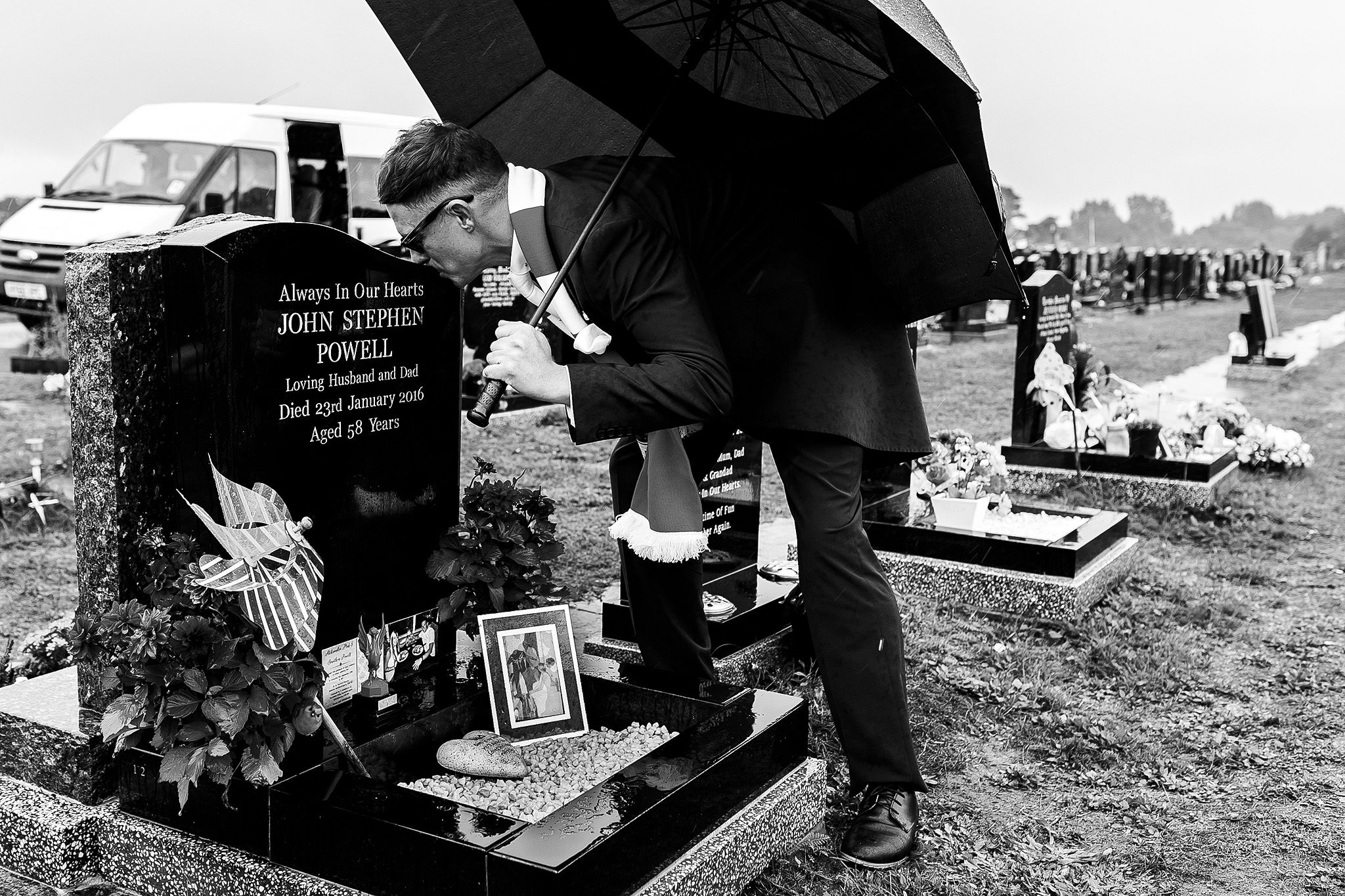 Groom holding umbrella leaning over to kiss head of grave stone