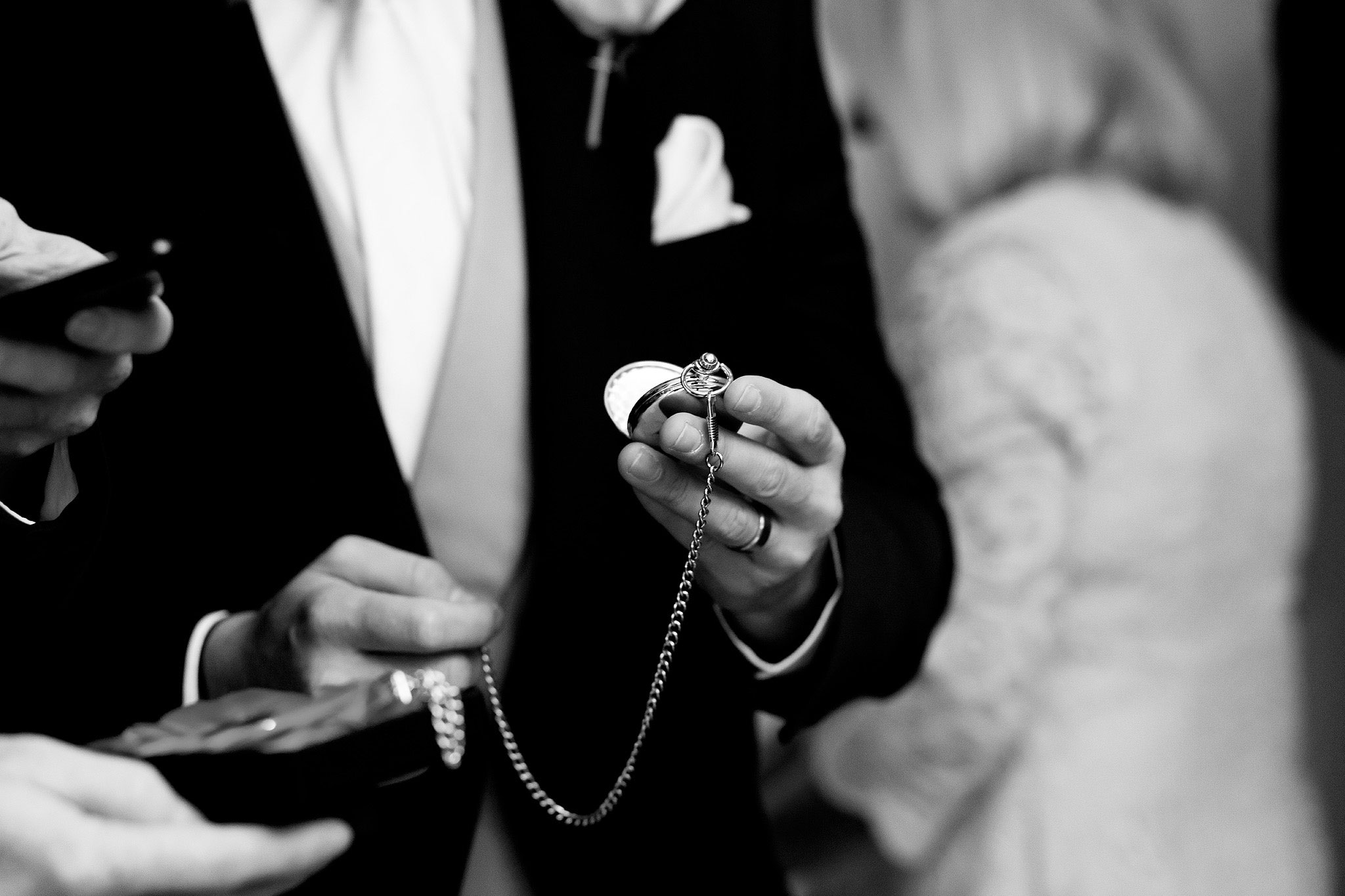 Black and white image of groom holding pocket watch