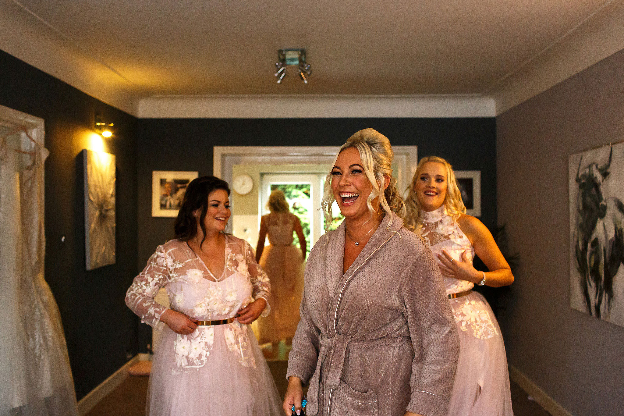 Bride with blonde hair laughing as she looks out the window with bridesmaids behind her
