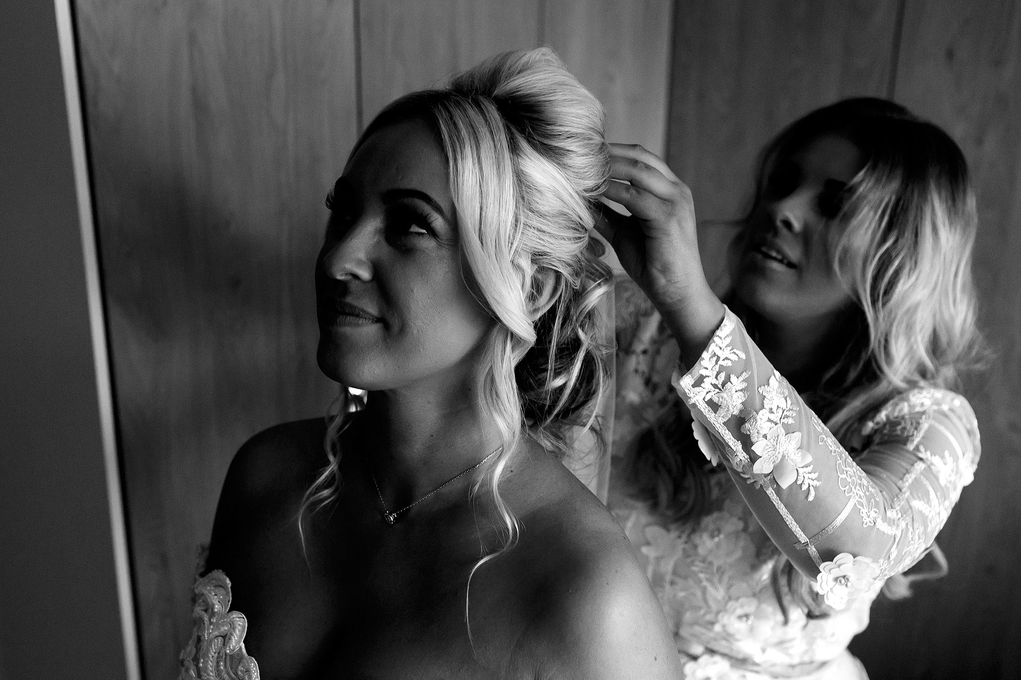 Black and white image with bride having veil put in by bridesmaid