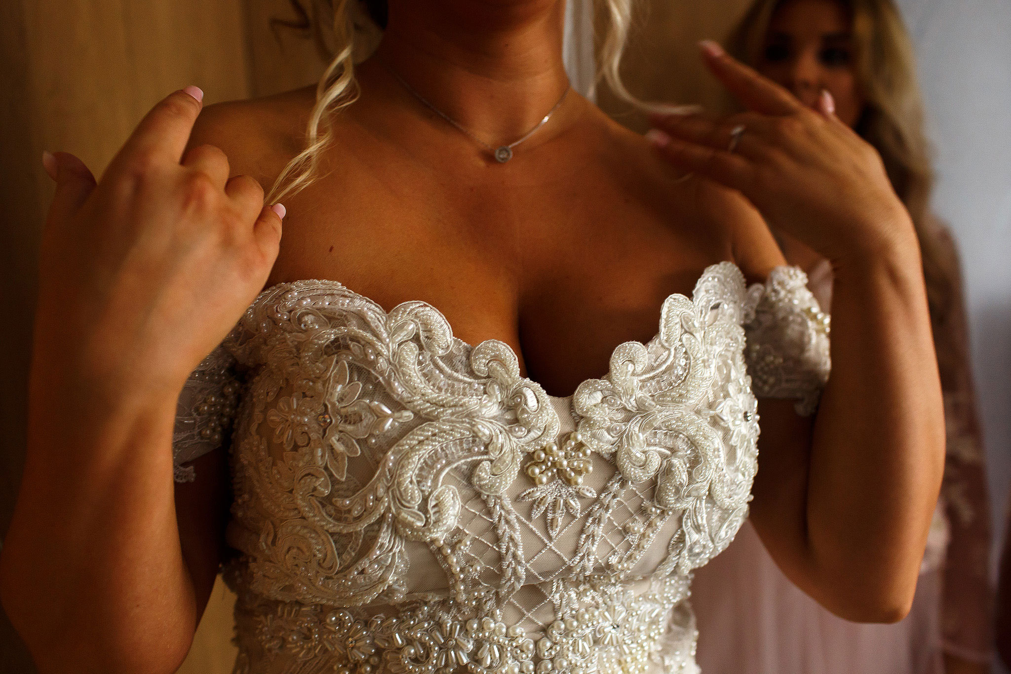 Bride wearing strapless wedding dress with beading, touching her blonde hair with hands