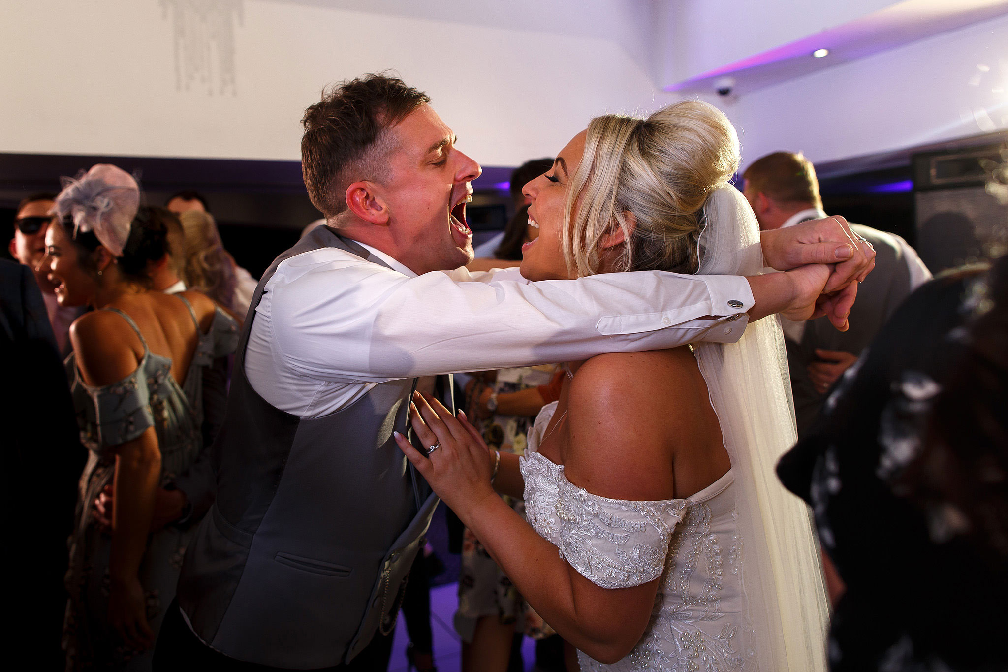 Bride and groom screaming into each others faces on the dance floor at Hurlston Hall Wedding