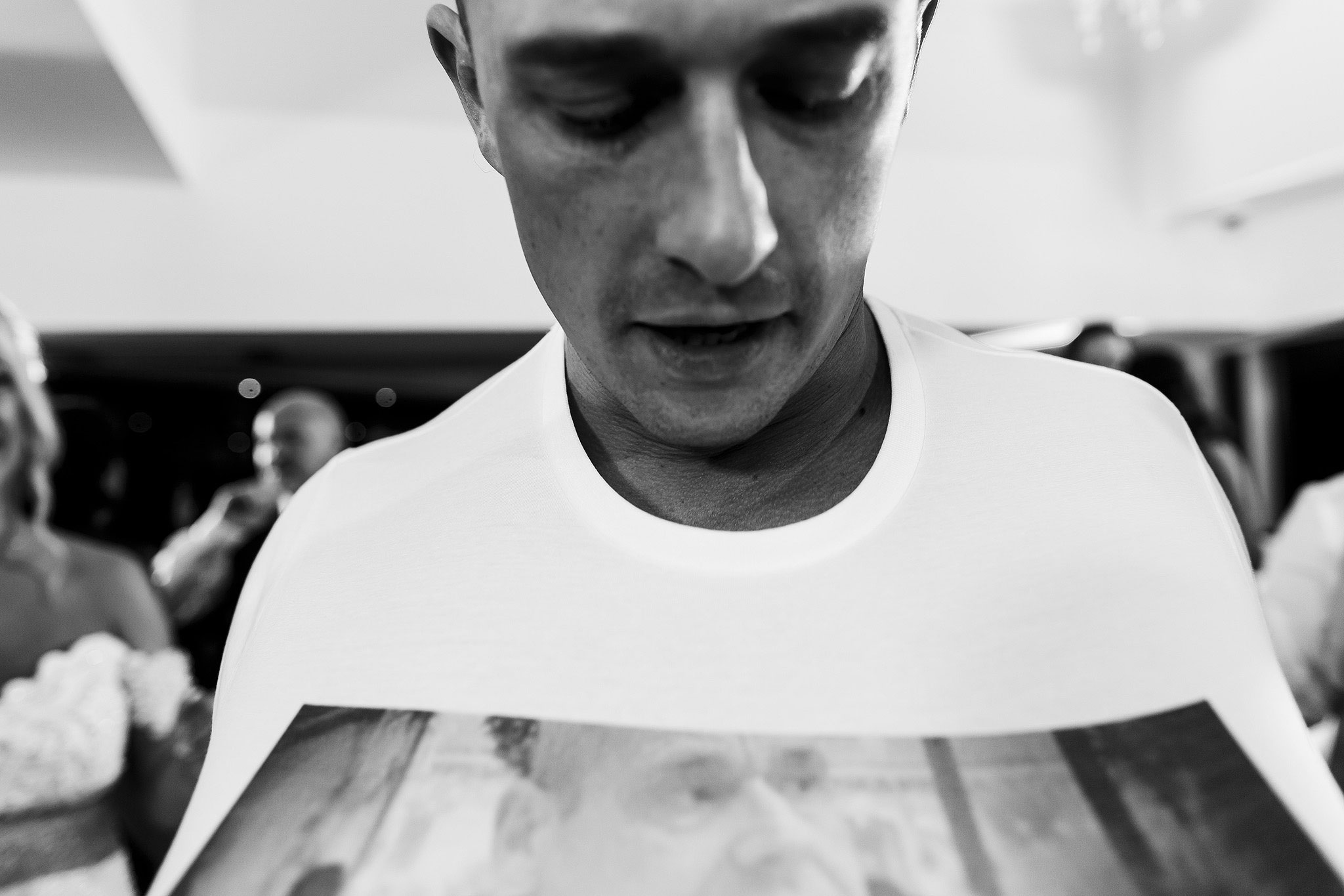 Black and white photograph of groom looking down at his t shirt