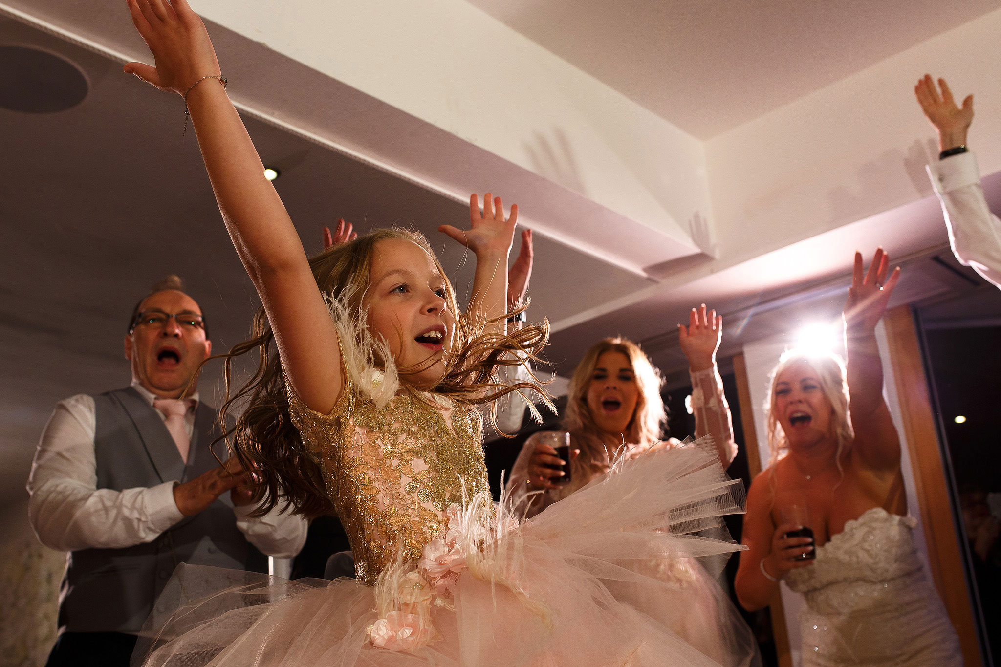 Flower girl throwing hands in the air on the wedding dance floor