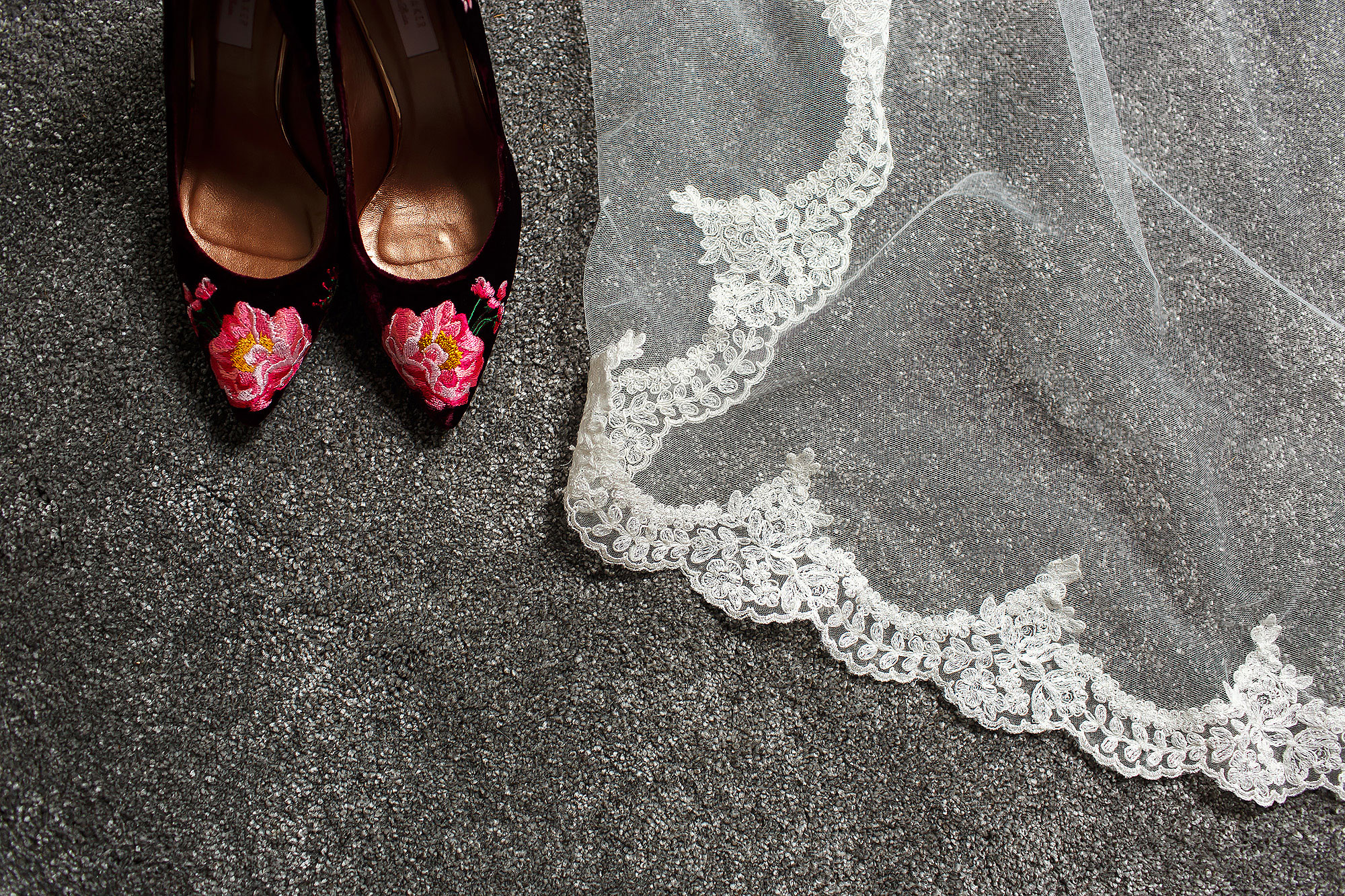 Burgundy Ted Baker Wedding Wedding Shoes placed next to laced veil - The Out Barn at Clough Bottom Wedding Photography