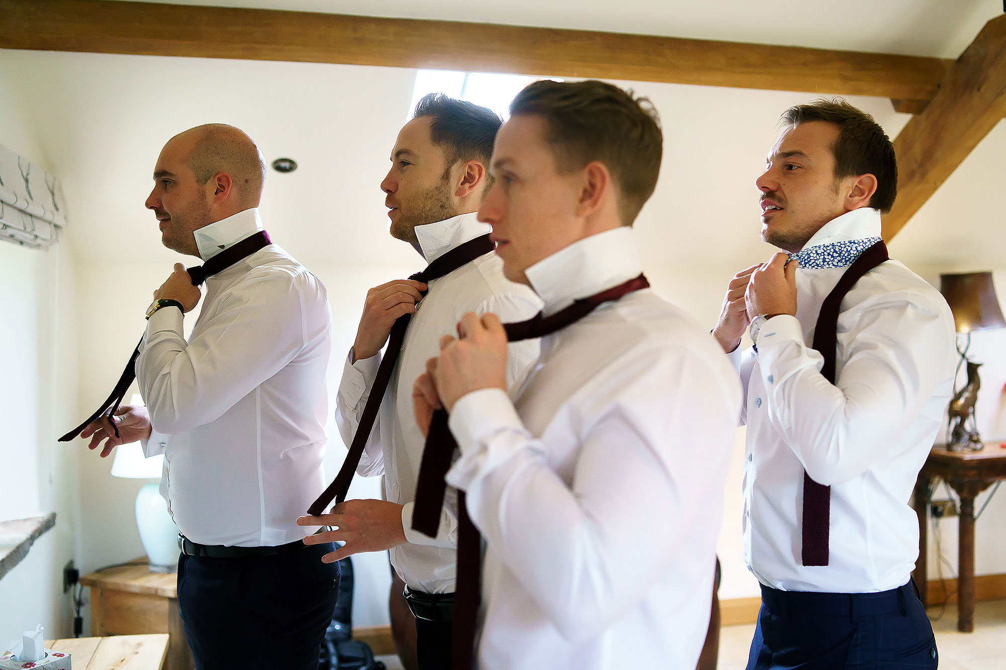 Groom and groomsmen lined up wearing white shirts fastening ties - The Out Barn at Clough Bottom Wedding Photography