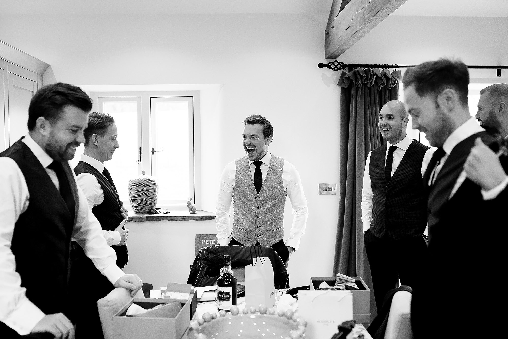 Groom laughing as he opens presents on the morning of his wedding - The Out Barn at Clough Bottom Wedding Photography