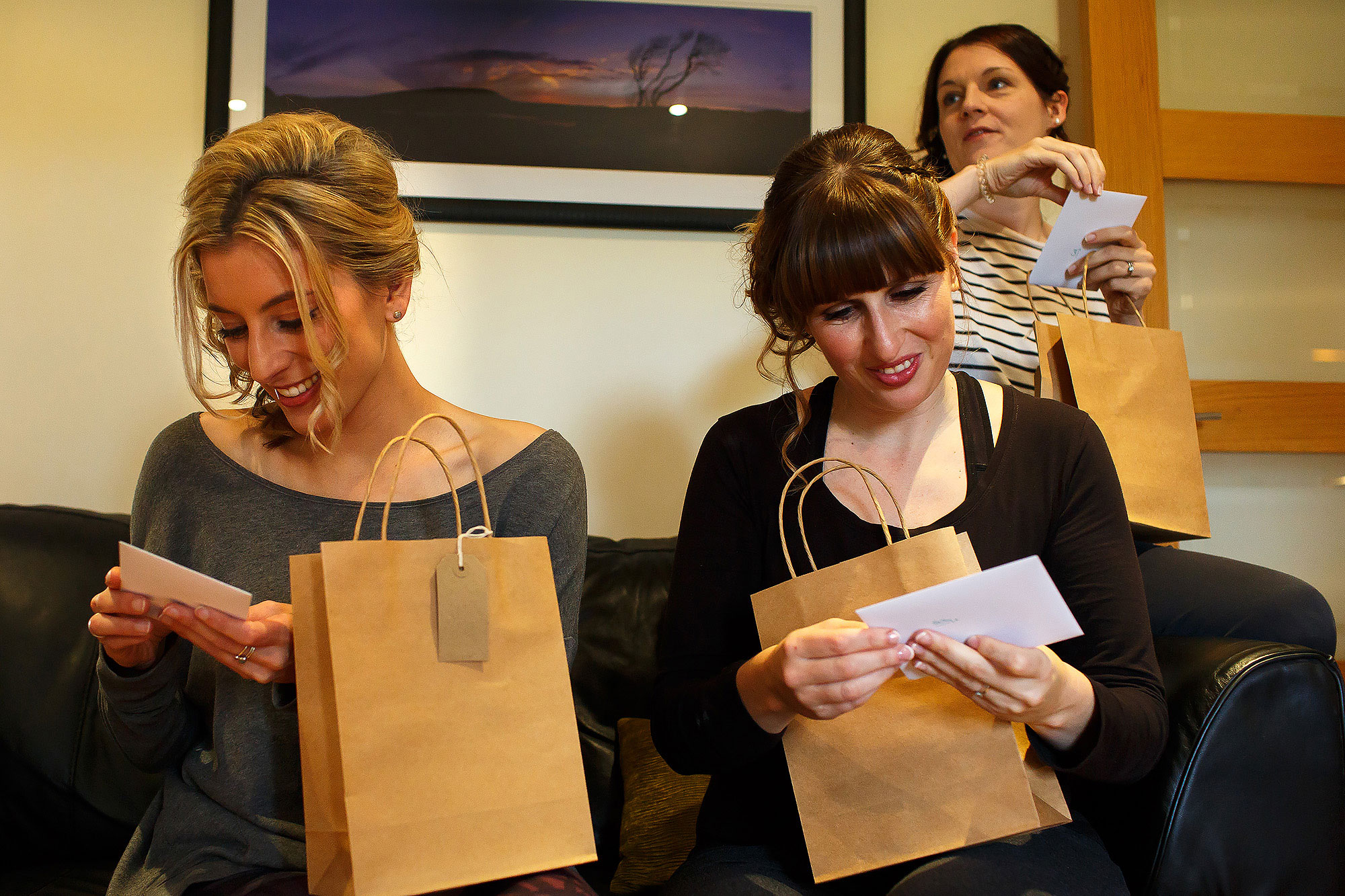 Bridesmaids opening wedding presents in brown paper bags - The Out Barn at Clough Bottom Wedding Photography