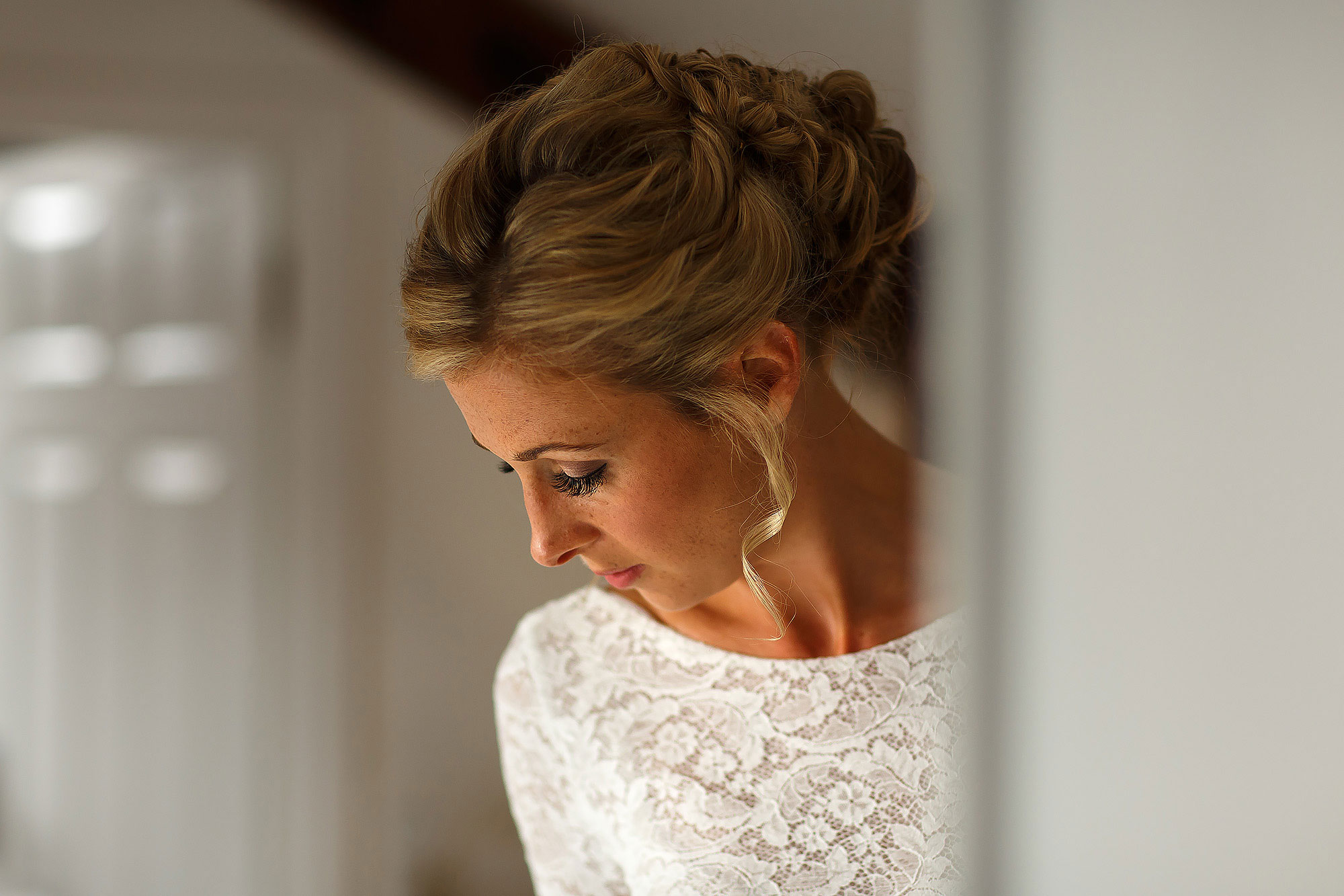 Bride with blonde hair pinned back looking down towards her lace wedding dress - The Out Barn at Clough Bottom Wedding Photography