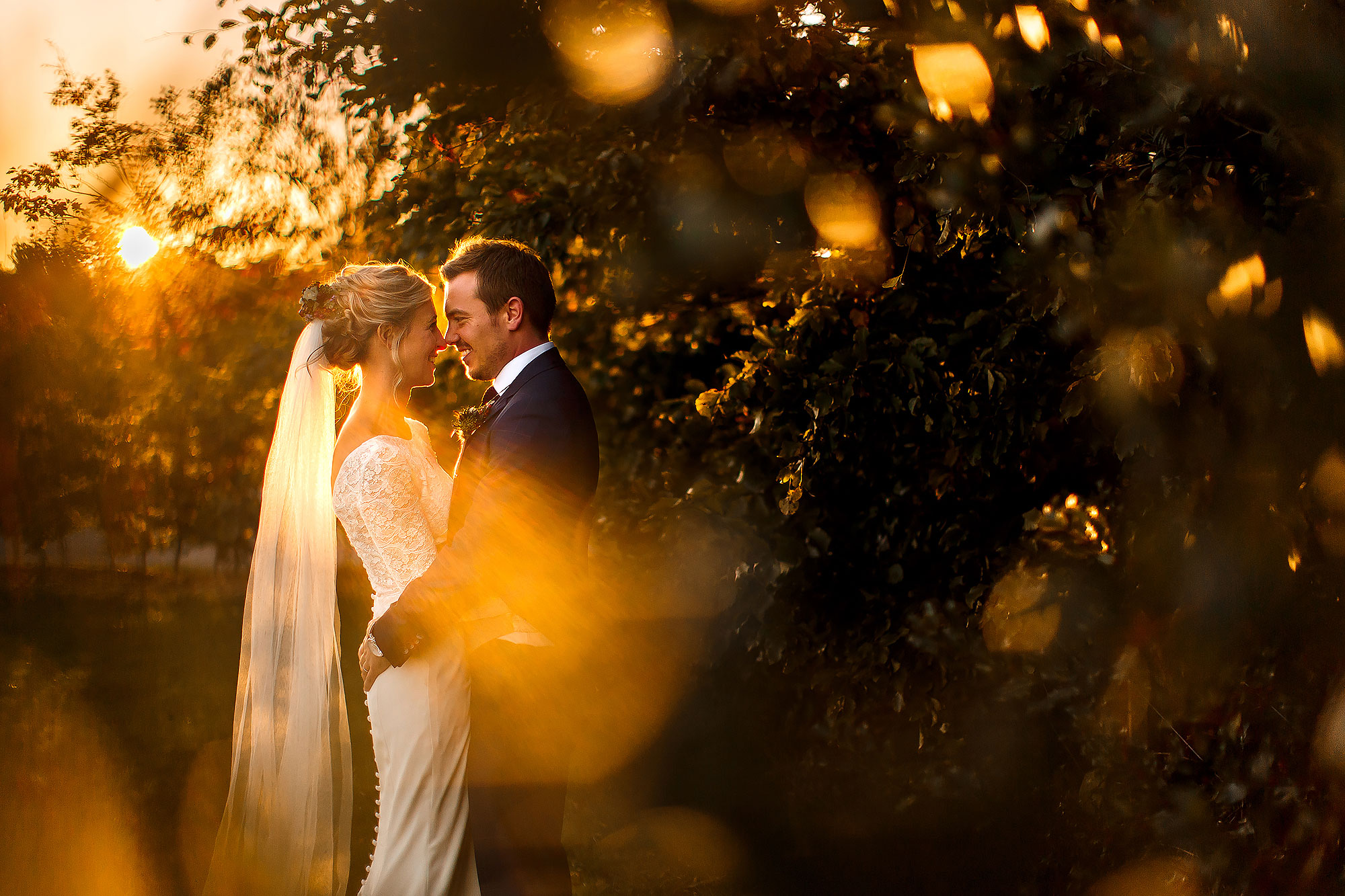 Bride and Groom in the gardens during golden hour sunset photoshoot with bokeh - The Out Barn at Clough Bottom Wedding Photography