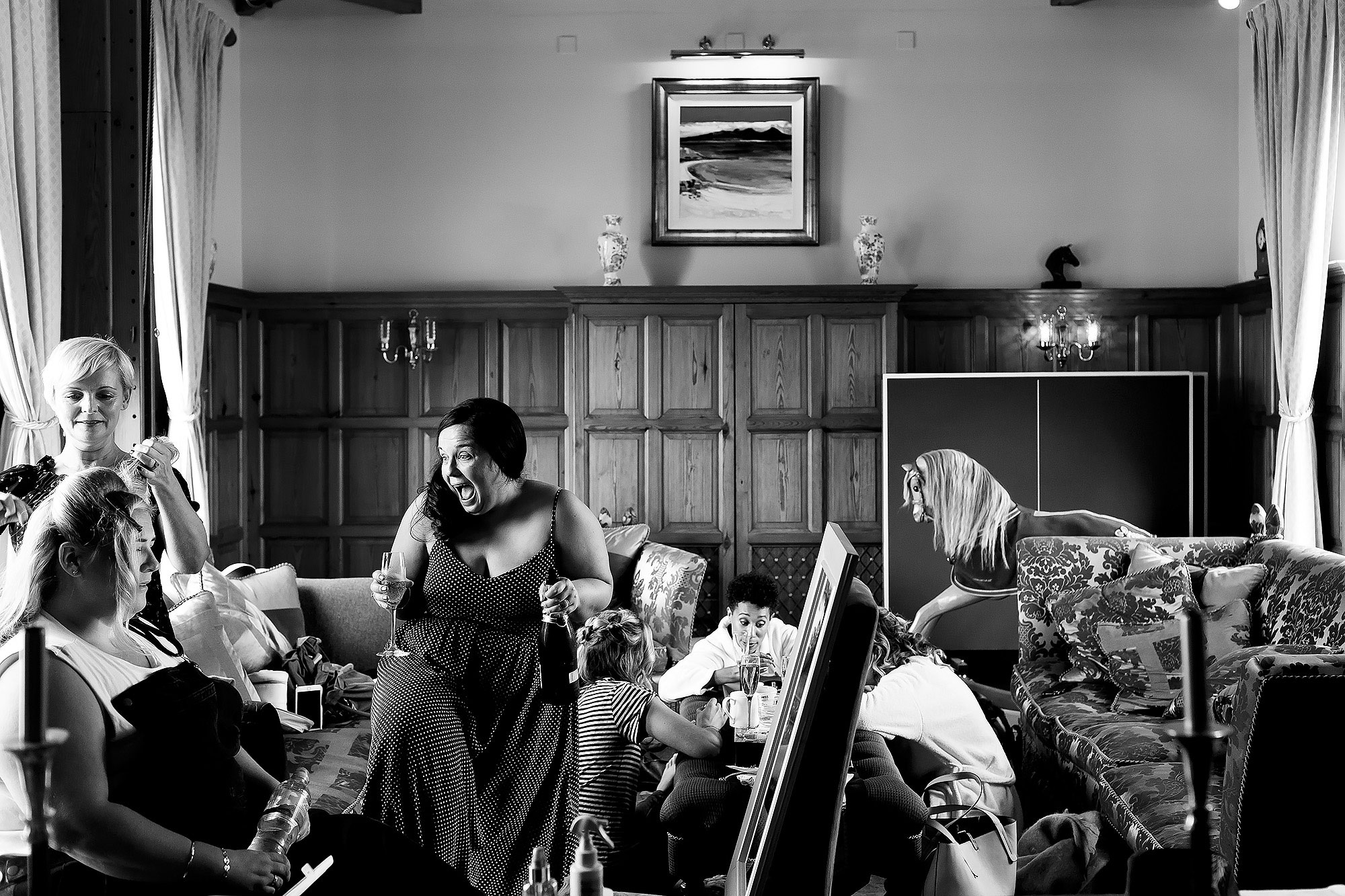 Documentary wedding scene with bridesmaids cheering holding champagne having their hair and make up applied | Lake District Wedding by Toni Darcy Photography