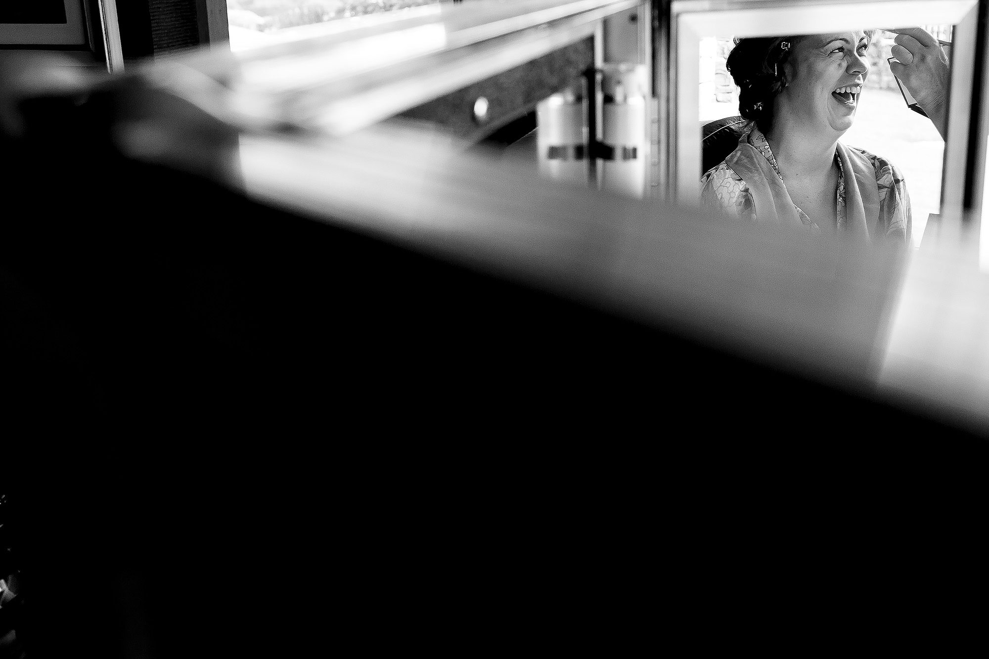 Brides reflection in a 3 way mirror as she laughs at the make up artist | Lake District Wedding by Toni Darcy Photography