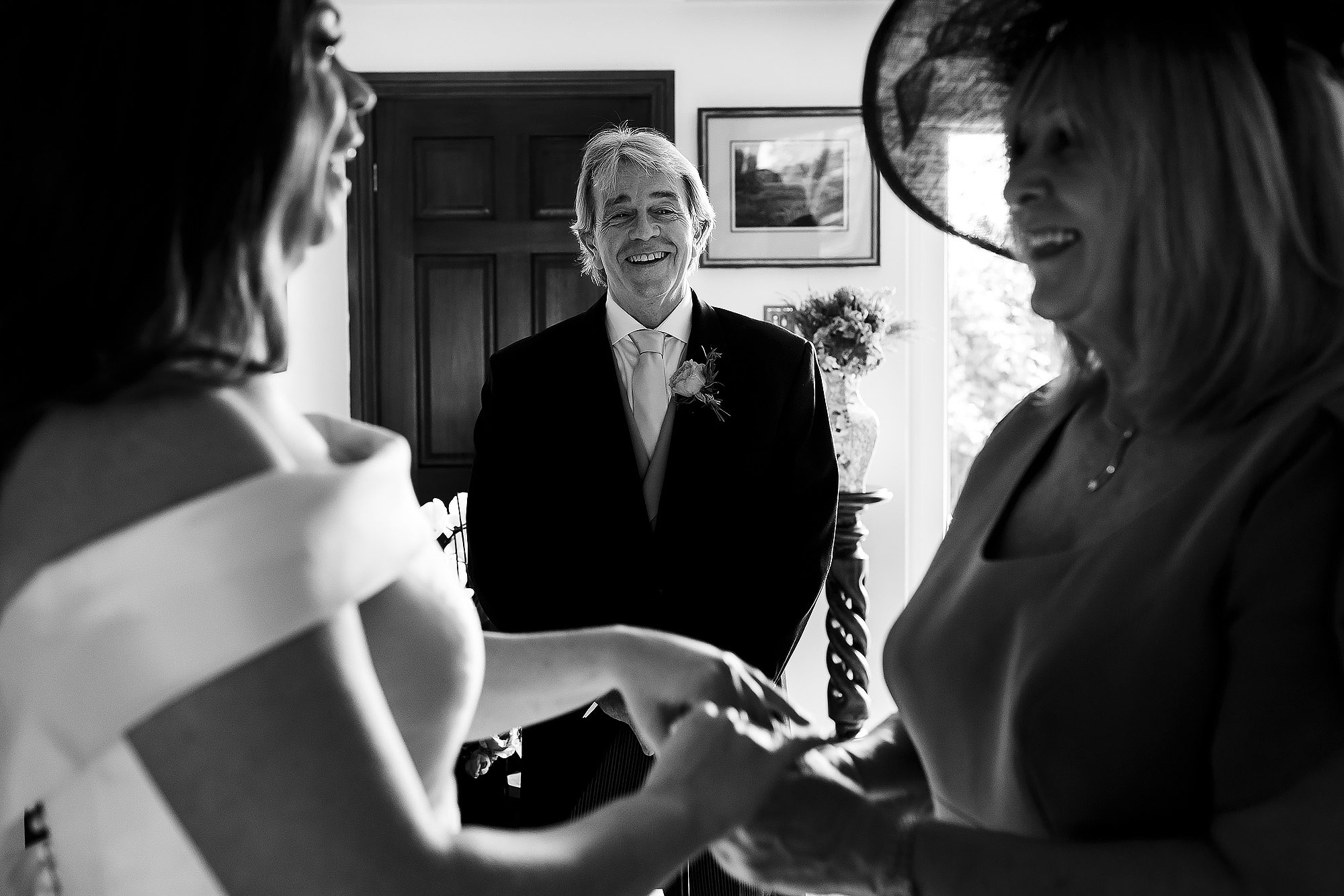 Father of the bride looking towards Bride and mother as they share a moment holding hands | Lake District Wedding by Toni Darcy Photography