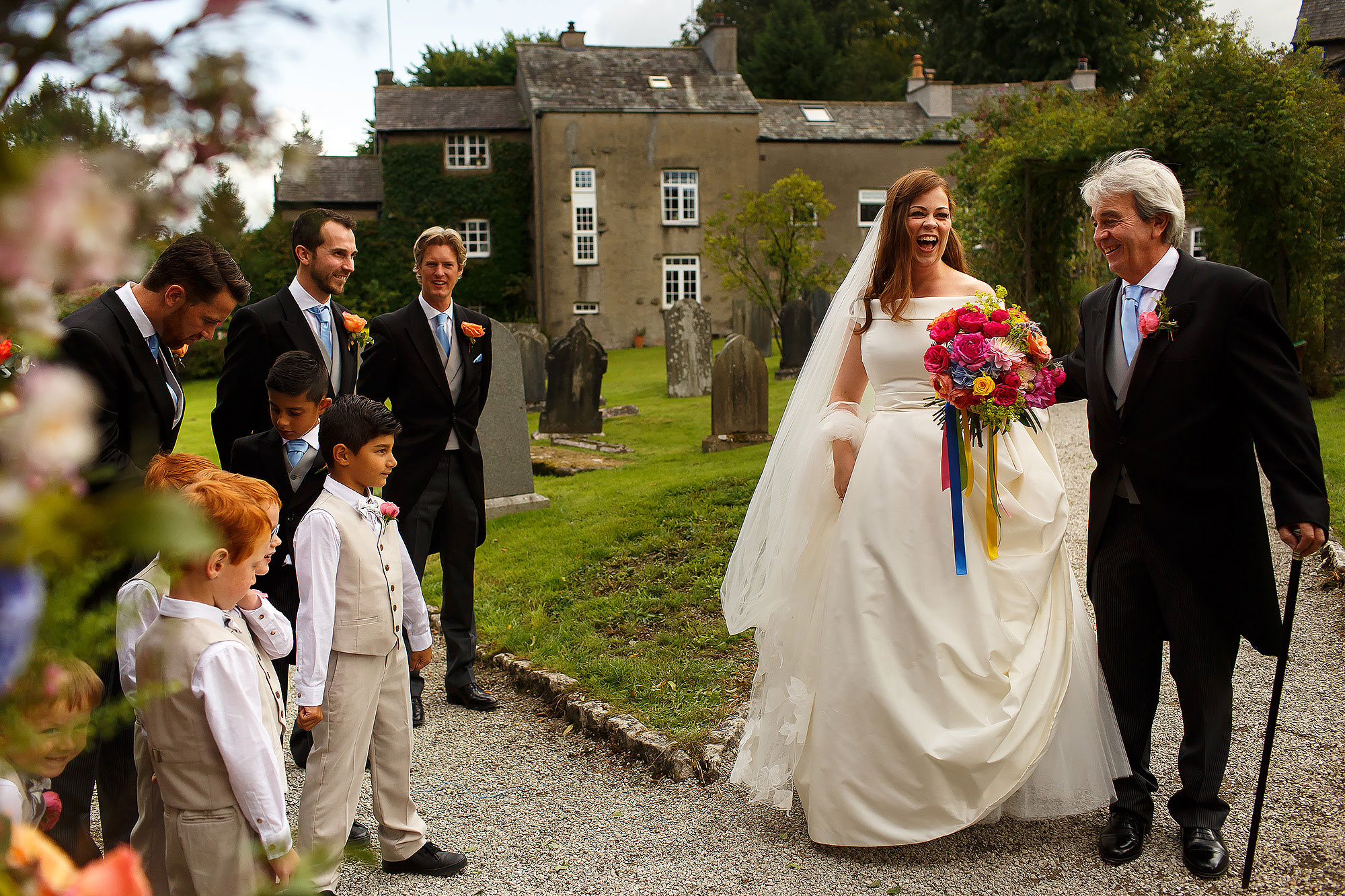 Bride arriving at church with colourful wedding bouquet with ribbons, wearing off the shoulder silk wedding dress and long floor length veil in the arms of her father | Lake District Wedding by Toni Darcy Photography