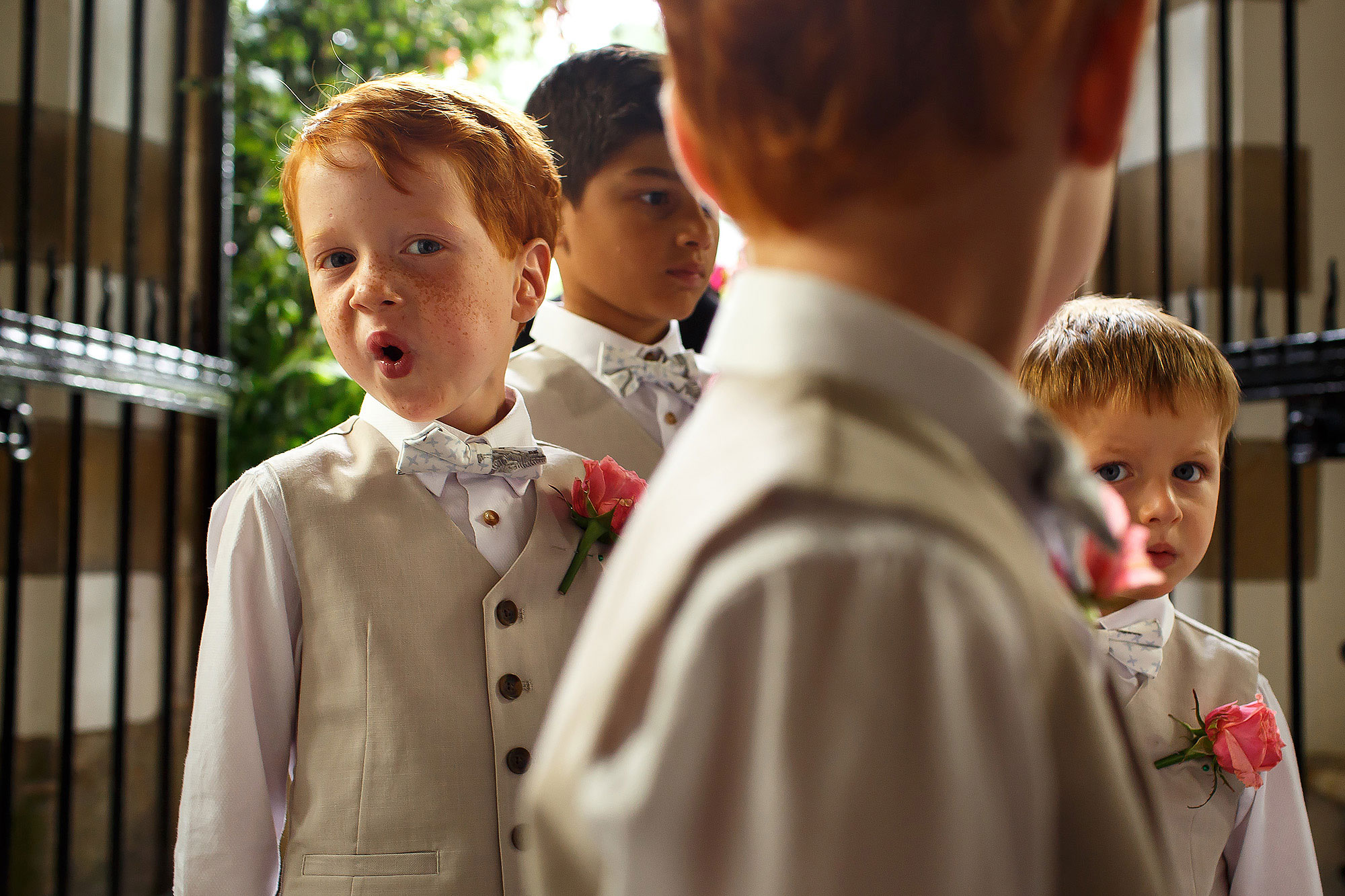 Page boys wearing linen 3 piece cream suits yawning as they line up to enter the church | Lake District Wedding by Toni Darcy Photography