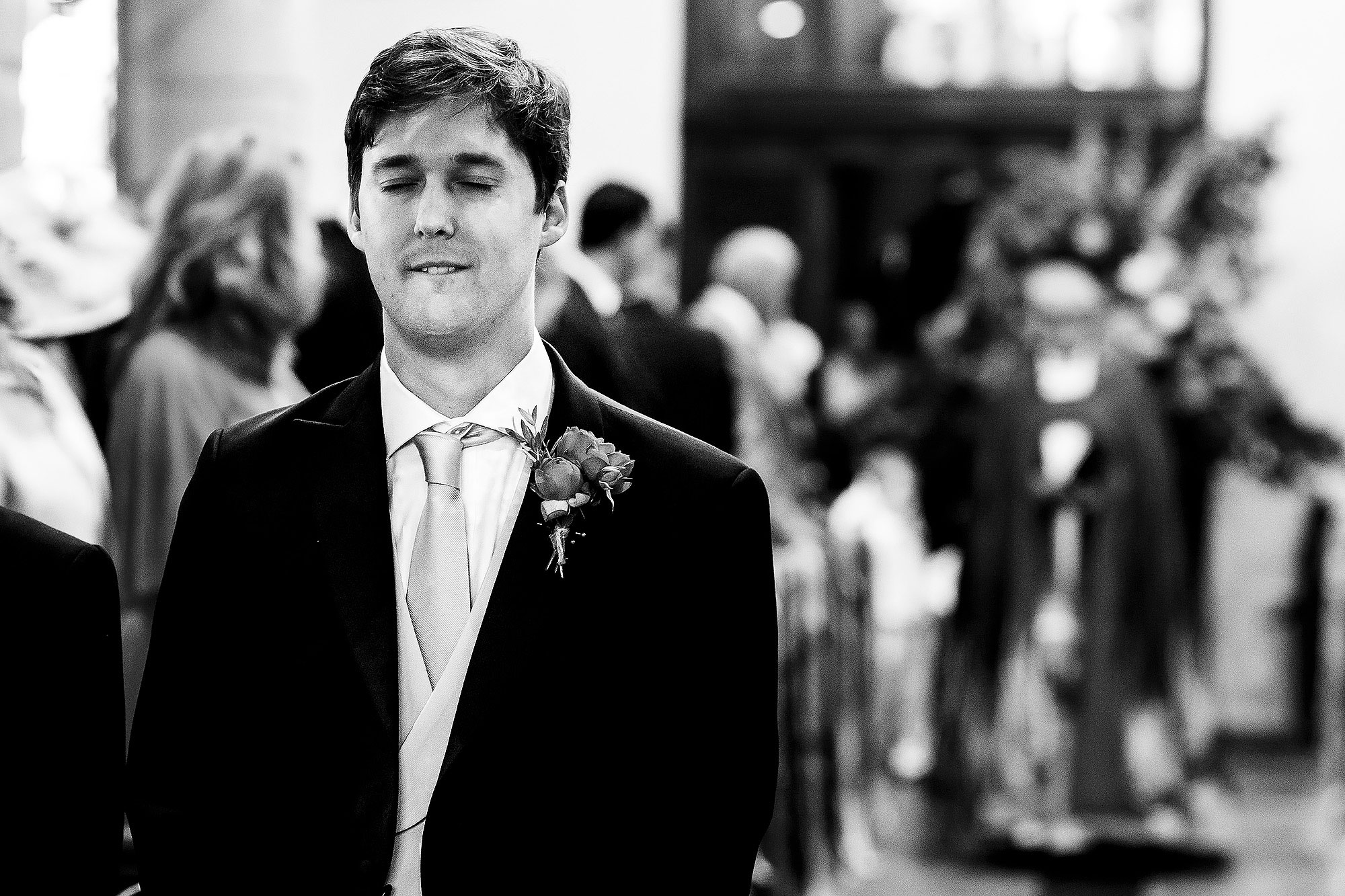 Groom closing eyes and biting lip as he nervously waits at the top of the aisle in church | Lake District Wedding by Toni Darcy Photography