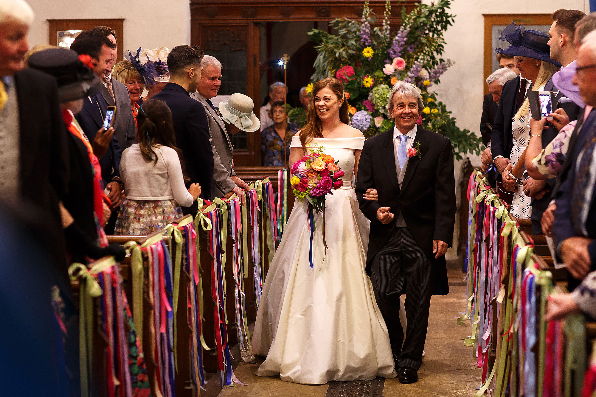 Bride with red hair and simple off the shoulder silk wedding dress walking down the aisle holding colourful floral bouquet with each church pew draped in colourful ribbons | Lake District Wedding by Toni Darcy Photography
