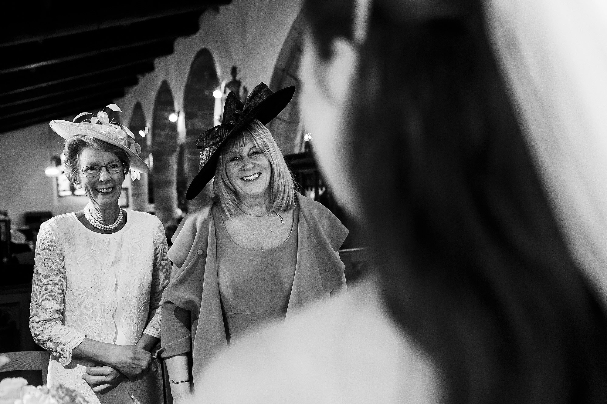 Wedding guests smiling looking towards the bride as she signs the wedding register | Lake District Wedding by Toni Darcy Photography