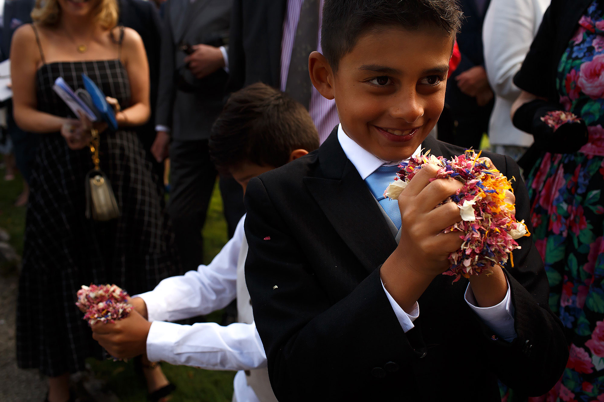 Page boys wearing navy suits and pale blue ties holding a very large handful of colourful confetti | Lake District Wedding by Toni Darcy Photography