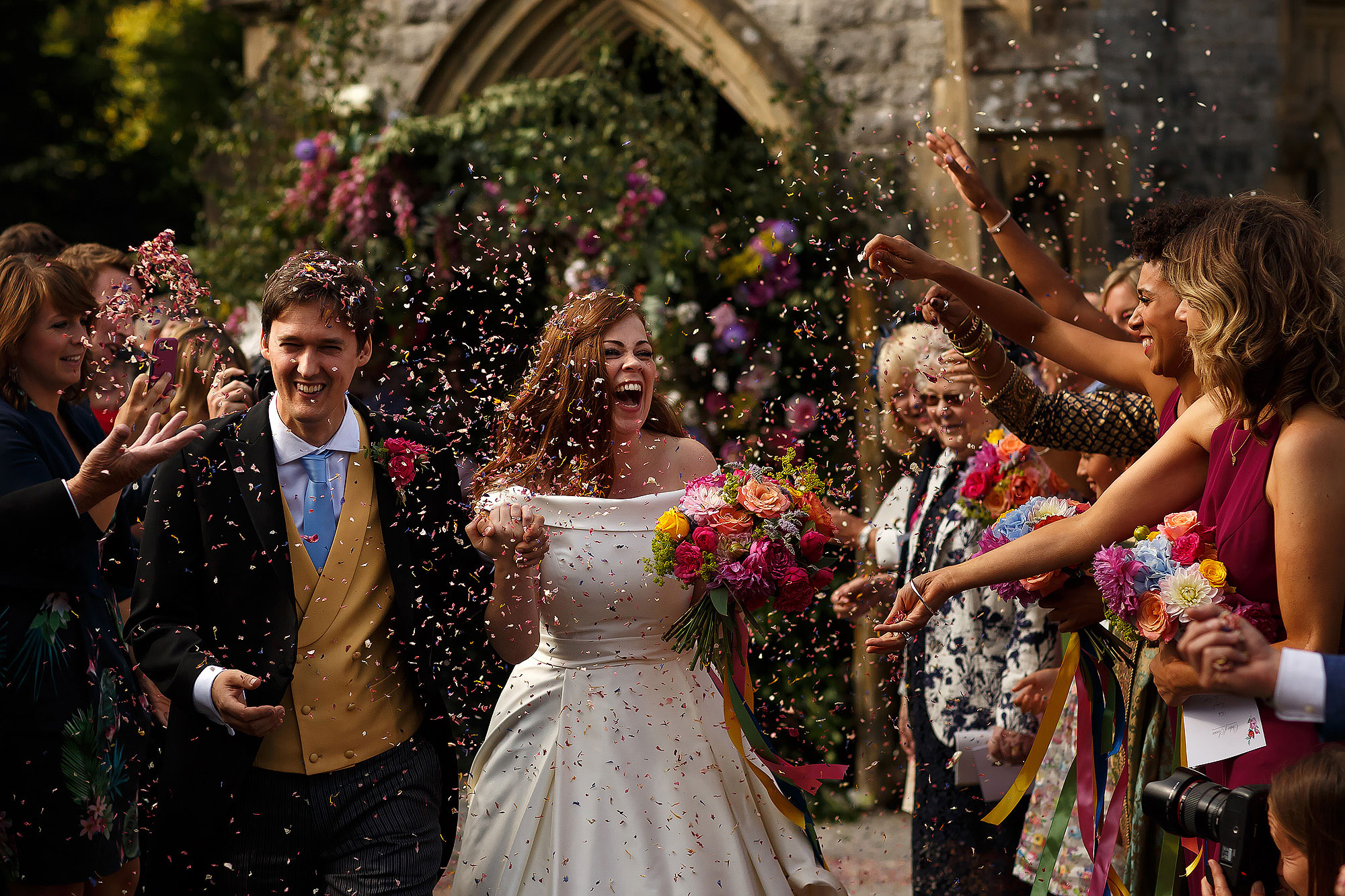 Bride with long red hair holding hands with groom wearing three piece walking through a colourful confetti storm outside church as wedding guests shower them in bright confetti