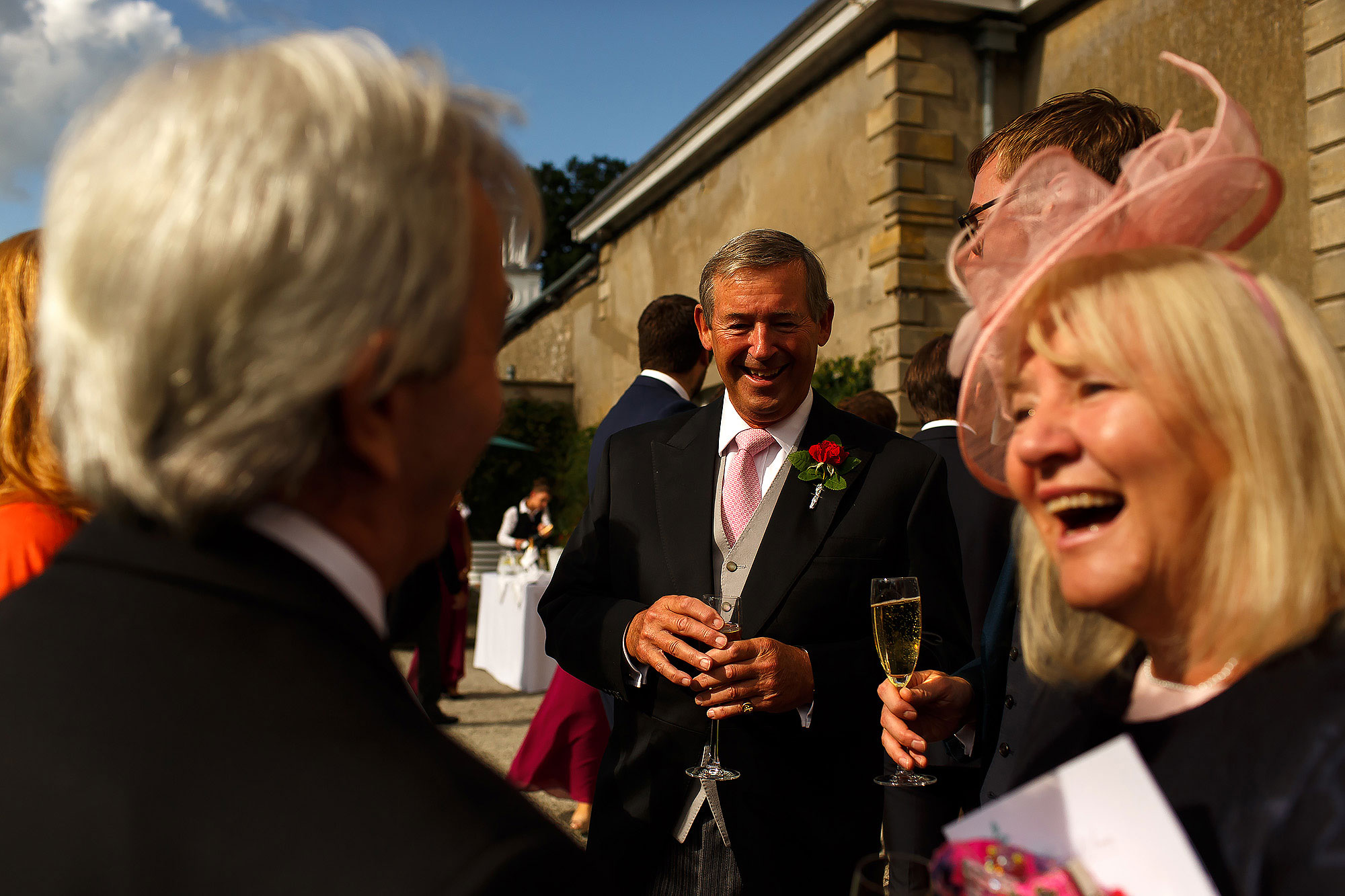 Wedding guests enjoying the sunshine as they drink fizz during wedding reception | Lake District Wedding by Toni Darcy Photography